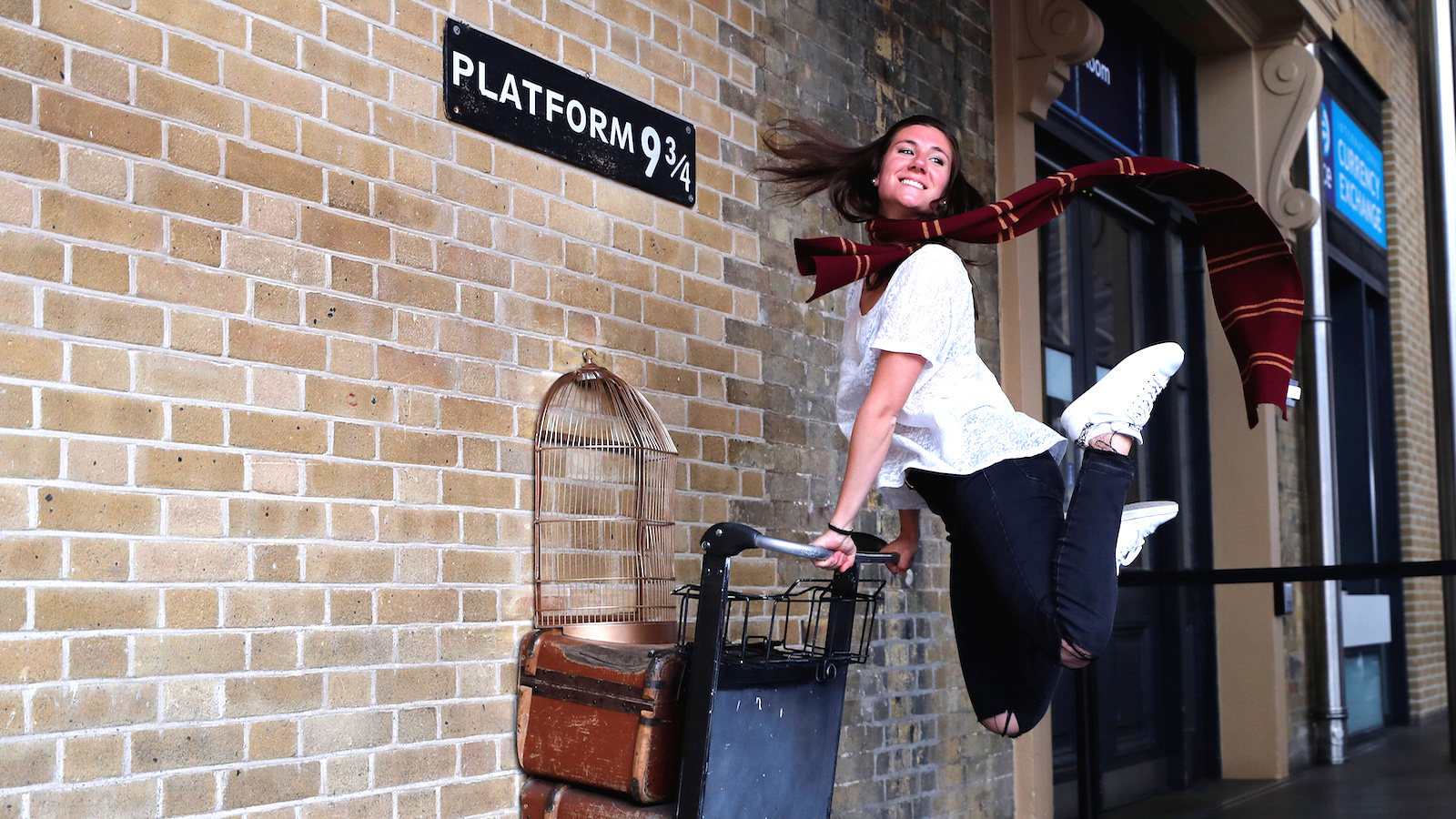A woman poses for a photograph with the Harry Potter trolley at Kings Cross Station, in London, Britain June 26, 2017. The first Harry Potter book, 'Harry Potter and the Philosopher's Stone' was first published 20 years ago.  REUTERS/Eddie Keogh - RTS18OOD