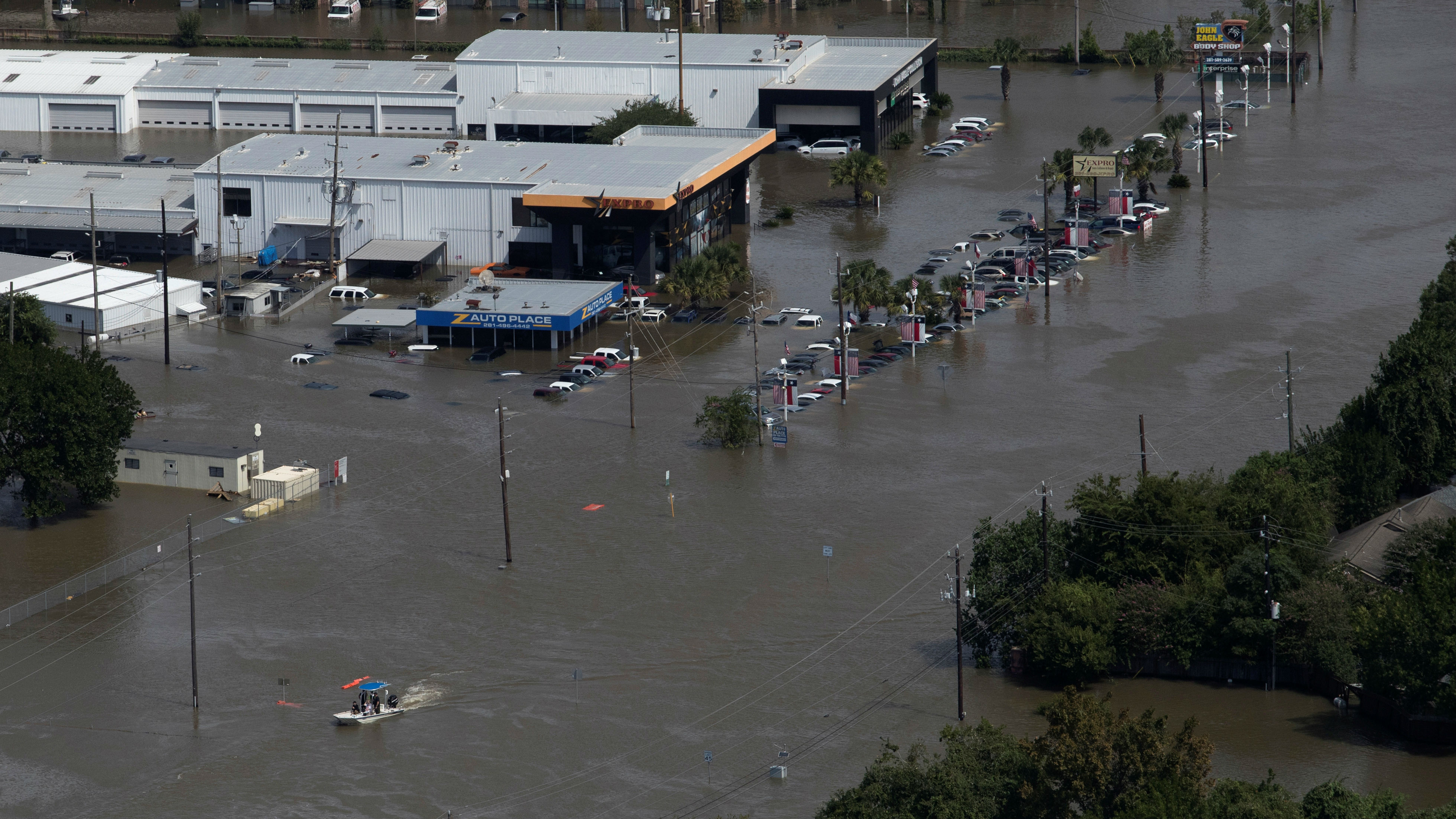 A boat looks for evacuees past businesses left flooded by Tropical Storm Harvey along Highway 6 in West Houston, Texas, U.S. August 30, 2017.