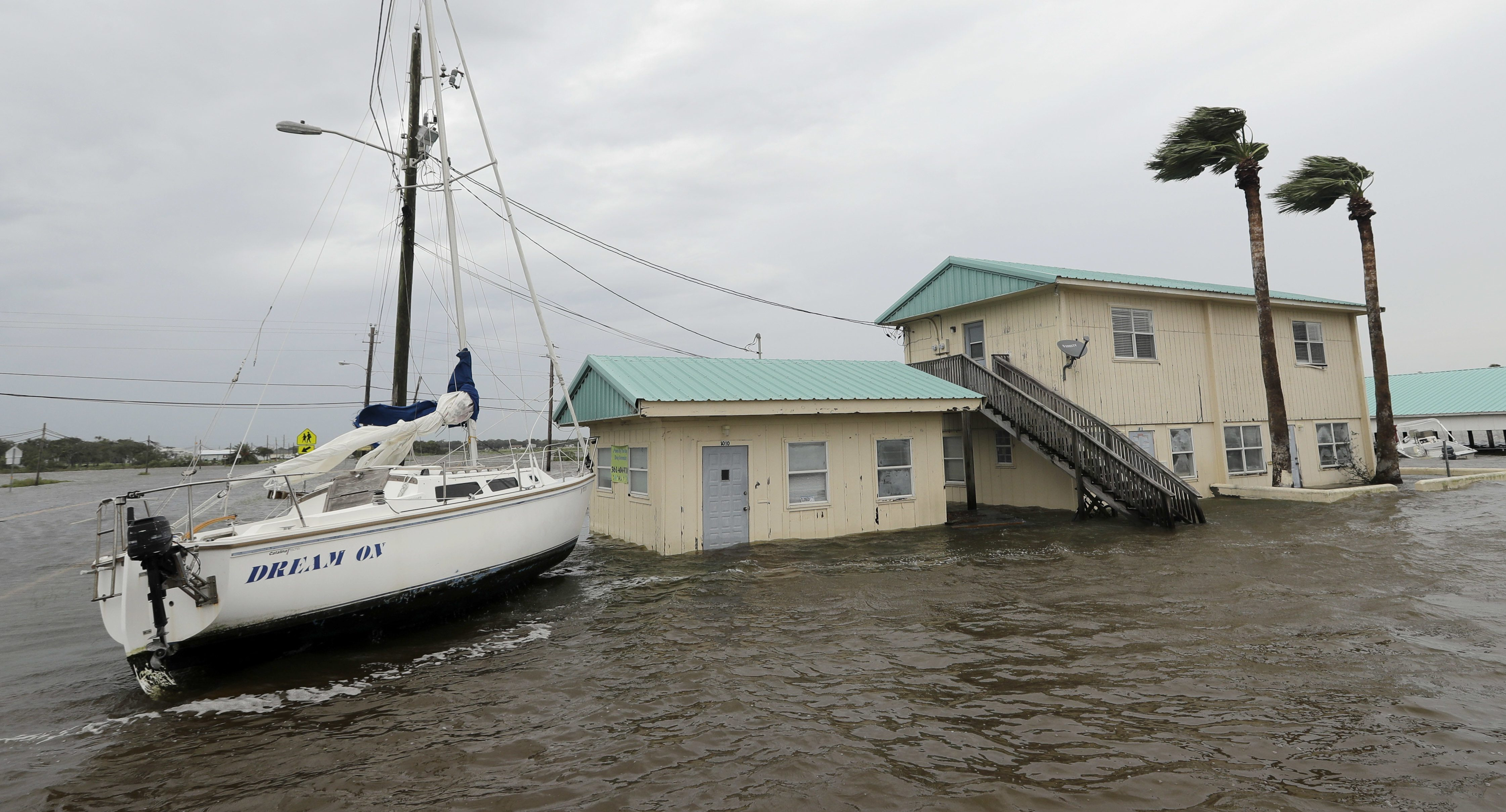 A sailboat sits in floodwaters next to a dog grooming business in the aftermath of Hurricane Harvey Saturday, Aug. 26, 2017, in Palacios, Texas. (AP Photo/David J. Phillip)