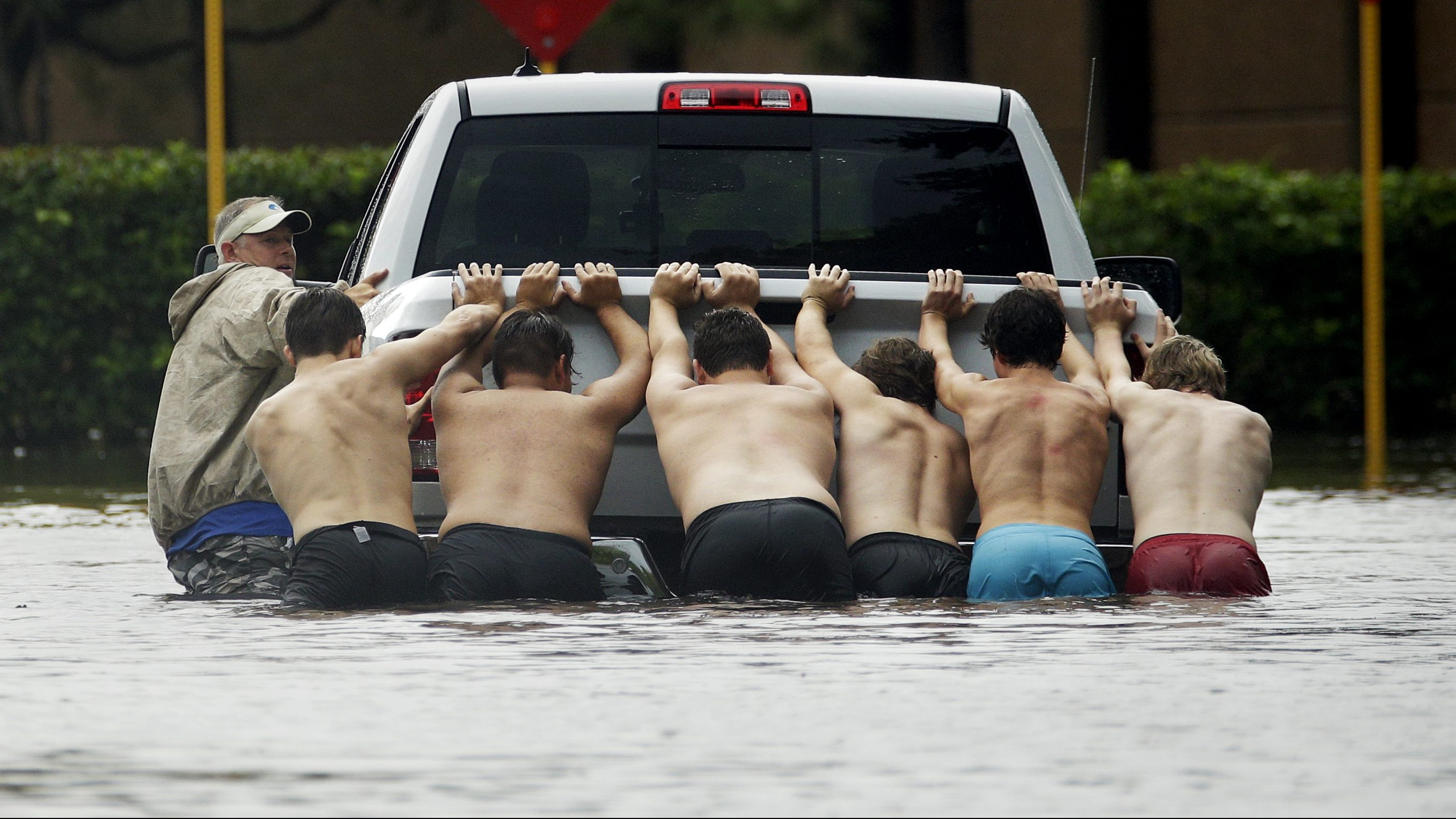 People push a stalled pickup through a flooded street in Houston, after Tropical Storm Harvey