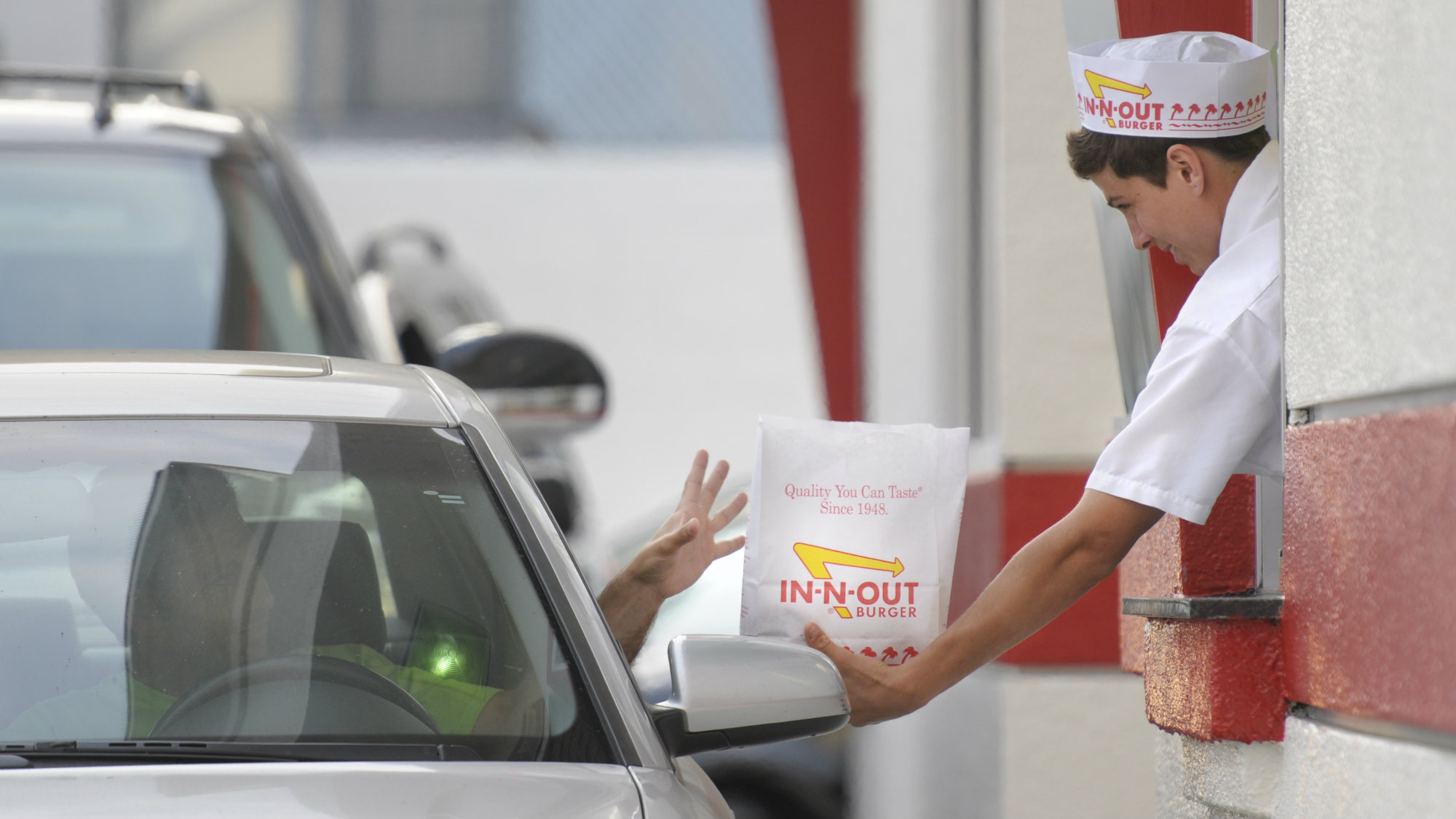 In this June 11, 2010 photo, a customer reaches for his order from the drive-through at In-N-Out Burger in the Hollywood area of Los Angeles.