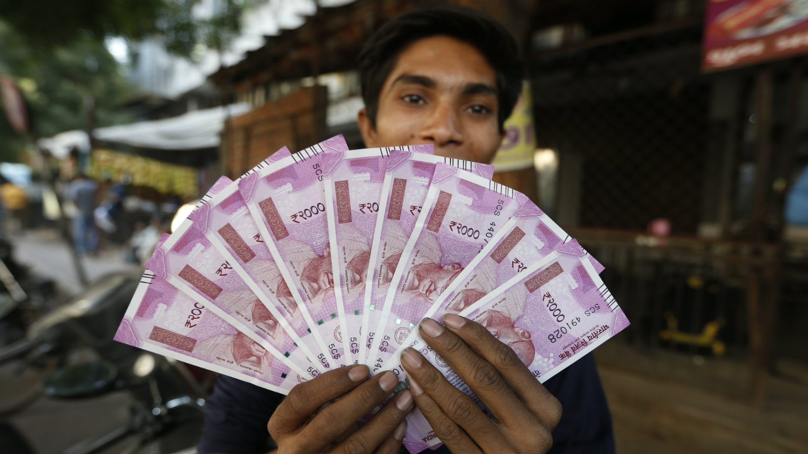 An Indian man displays new currency notes of 2000 Indian rupee in Ahmadabad, India, Friday, Nov. 11, 2016. Delivering one of India's biggest-ever economic upsets, Prime Minister Narendra Modi this week declared the bulk of Indian currency notes no longer held any value and told anyone holding those bills to take them to banks to deposit or exchange them.