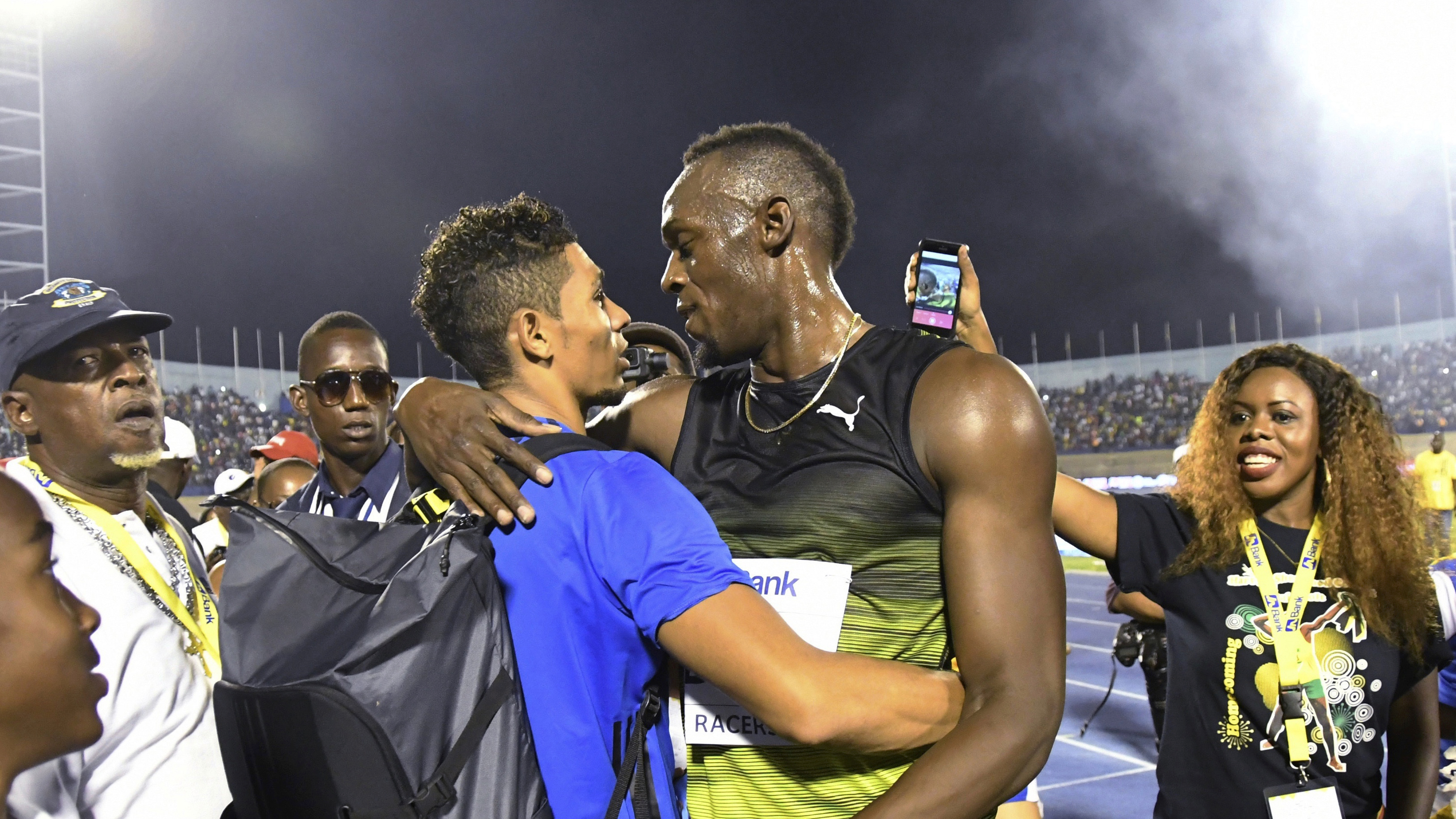 """Jamaica's Usain Bolt, center right, embraces South African sprinter Wayde van Niekerk after winning the """"Salute to a Legend"""" 100 meters during the Racers Grand Prix at the national stadium in Kingston, Jamaica, Saturday, June 10, 2017. Bolt started his final season with his last race on Jamaican soil and plans to retire from track and field after the 2017 London World Championships in August. (AP Photo/Bryan Cummings)"""
