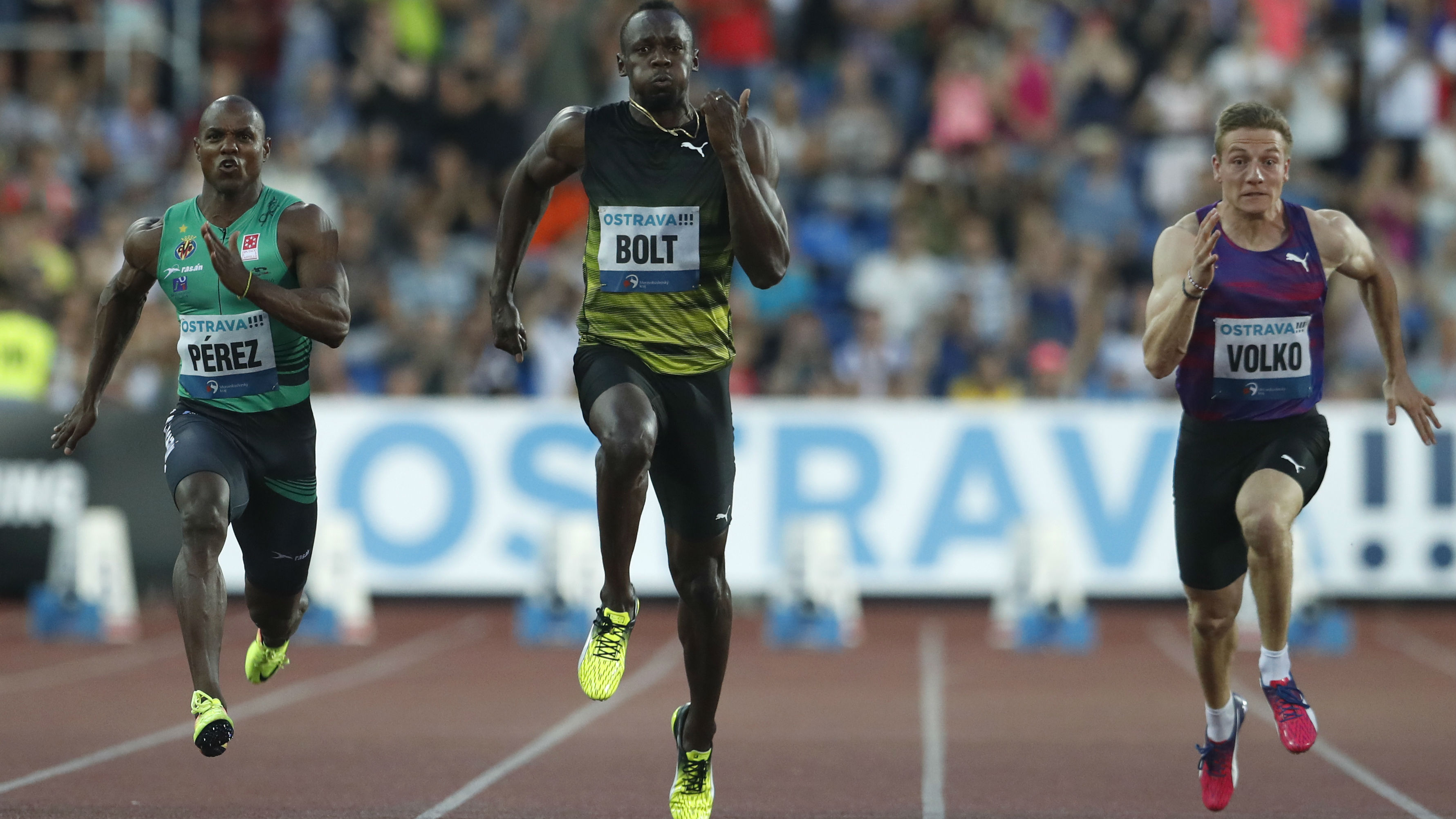 Usain Bolt running in between two other sprinters on a field.