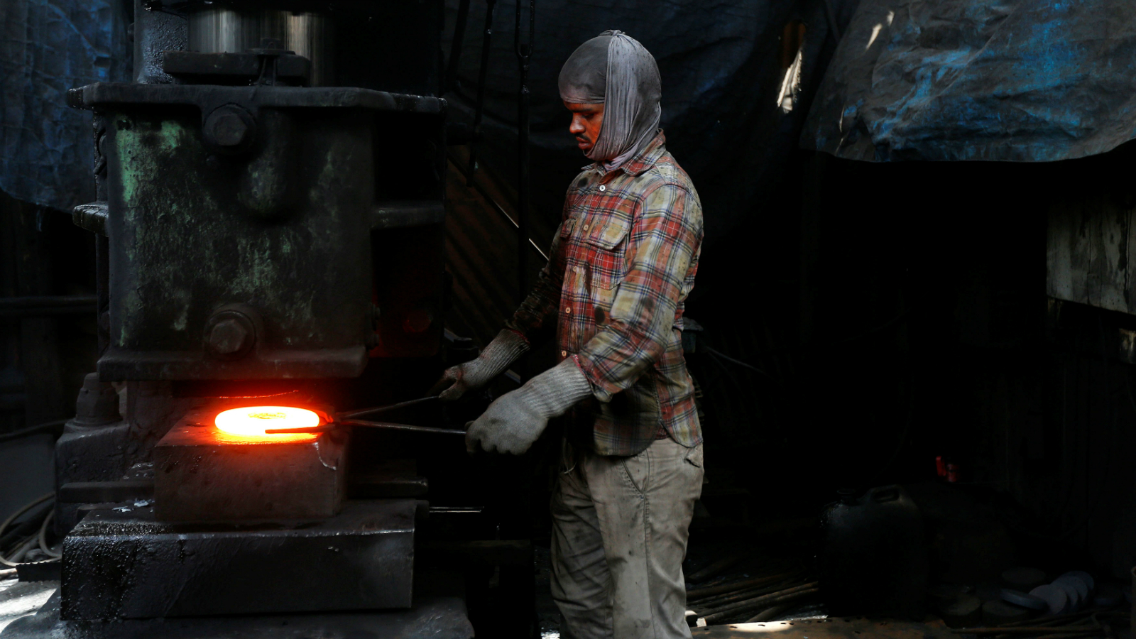 A worker forges a piece of metal in an industrial unit manufacturing automotive spare parts in Mumbai, India May 31, 2017.