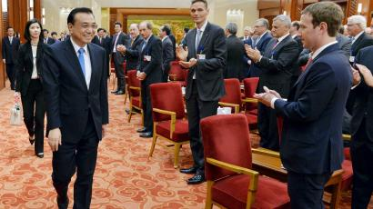 Facebook's Chief Executive Officer Mark Zuckerberg (R) and the overseas representatives of China Development Forum applaud for the arrival of Chinese Premier Li Keqiang at a meeting at Great Hall of the People in Beijing, China, March 21, 2016.