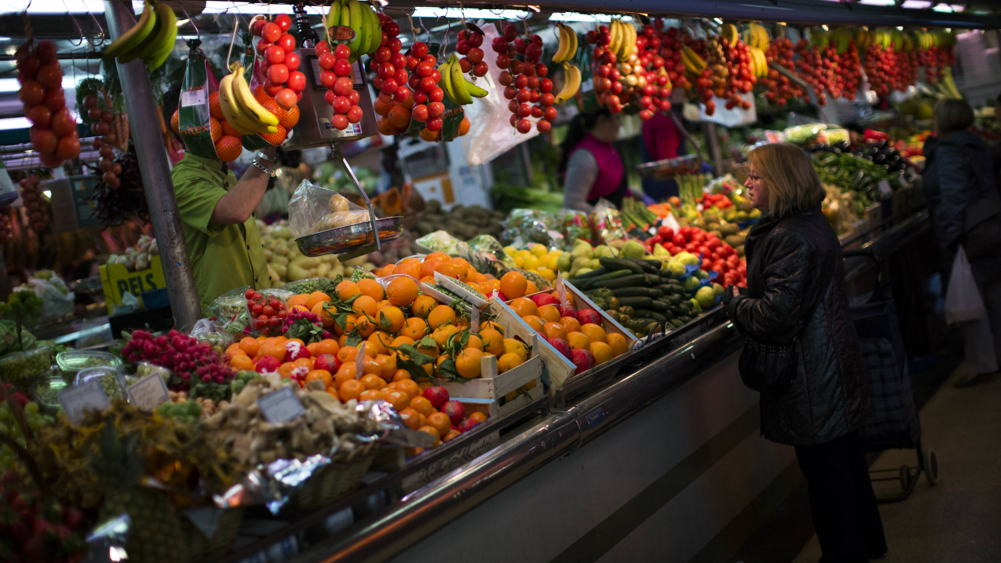 In this Thursday Jan. 17, 2013 file photo, a woman buys fruit at a market in Barcelona, Spain.