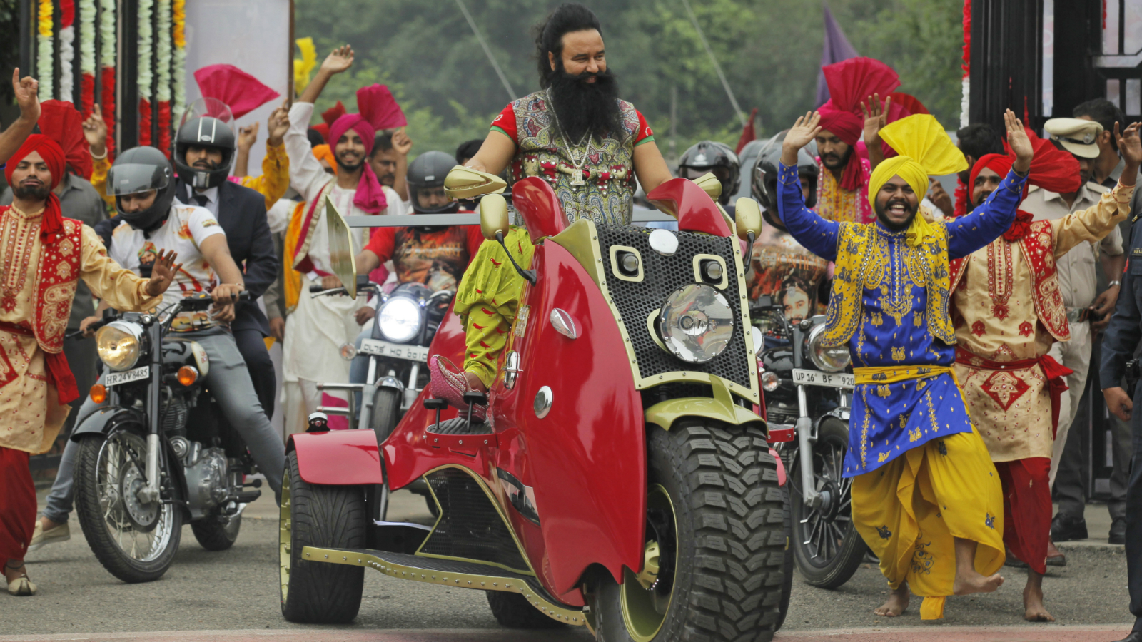"""In this Wednesday, Oct. 5, 2016 photo, Indian spiritual guru, who calls himself Saint Dr. Gurmeet Ram Rahim Singh Ji Insan, arrives for a press conference ahead of the release of his new film """"MSG, The Warrior Lion Heart,"""" in New Delhi, India. The leader of the quasi-religious sect has launched a film franchise in which he stars as Messenger of God, or MSG for short, with divine powers to save the world. He claims to have 50 million followers and runs a spiritual empire that promotes vegetarianism and campaigns against drug addiction. With a guaranteed audience among his followers, Insan said he's had little trouble getting his films released commercially in cinemas. (AP Photo/Tsering Topgyal, File"""