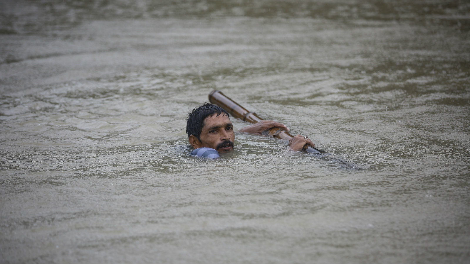 A man tries to cross flood water at Topa village in Saptari district, Nepal, 12 August 2017. According to media reports, nearly 18 people have died and thousands have been affected by floods as the Department of Hydrology and Meteorology warned of heavy rains for two days.