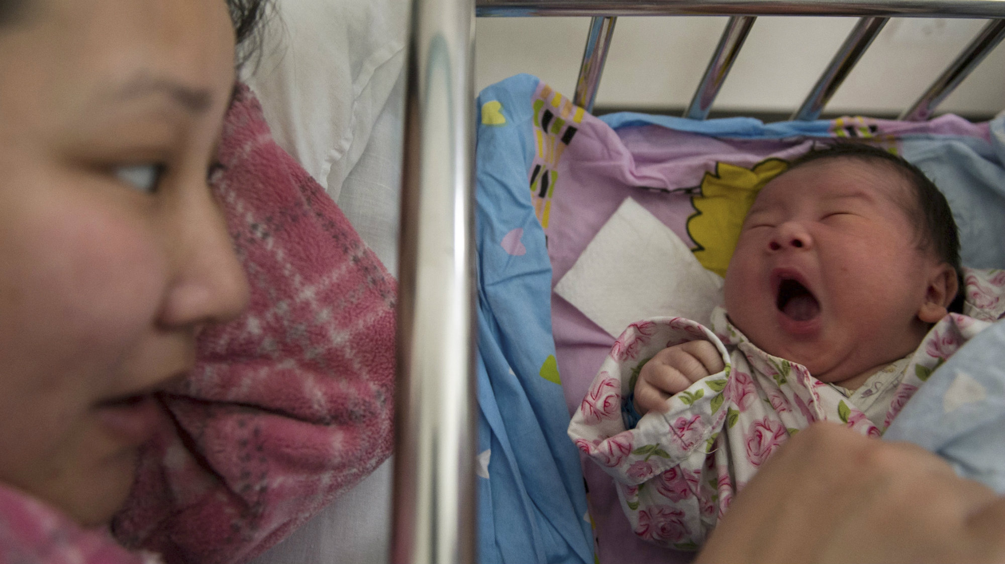 Li Yan (L) looks at her newborn baby at a hospital in Hefei, Anhui province February 23, 2014.