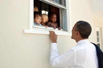 Former President Barack Obama looks into a window with babies from all ethnicities.