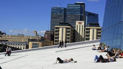 People lie in the sun outside the Oslo Opera House