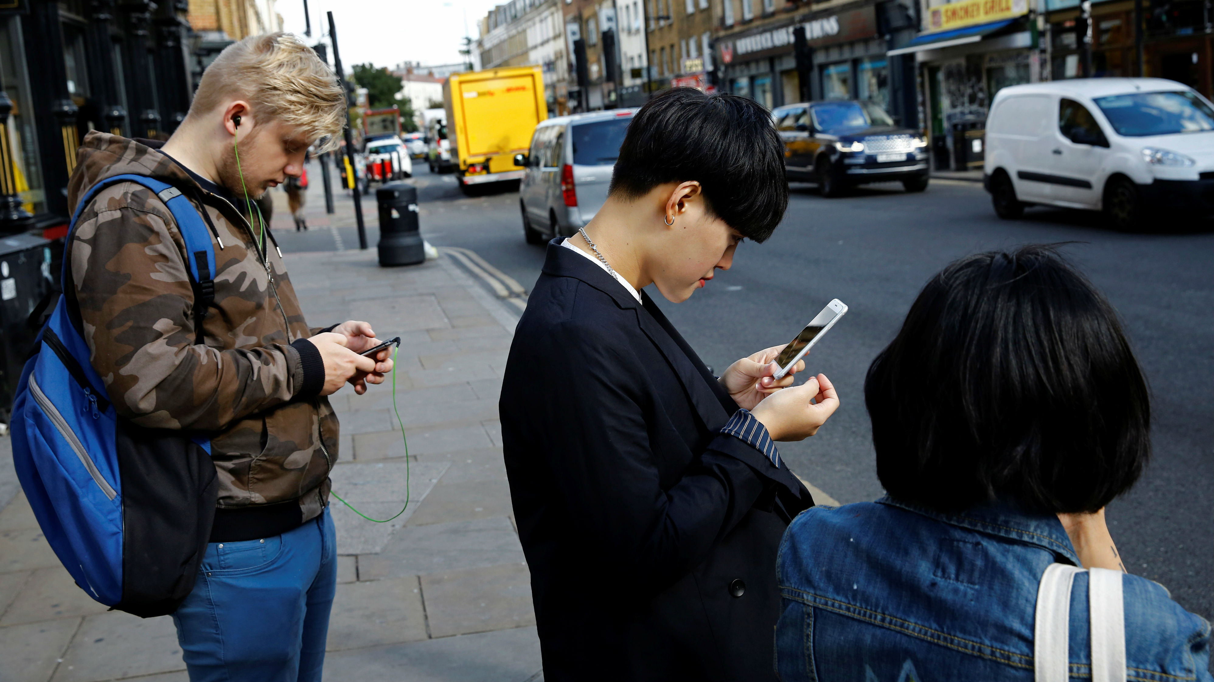 Three people looking at their phones on a street.