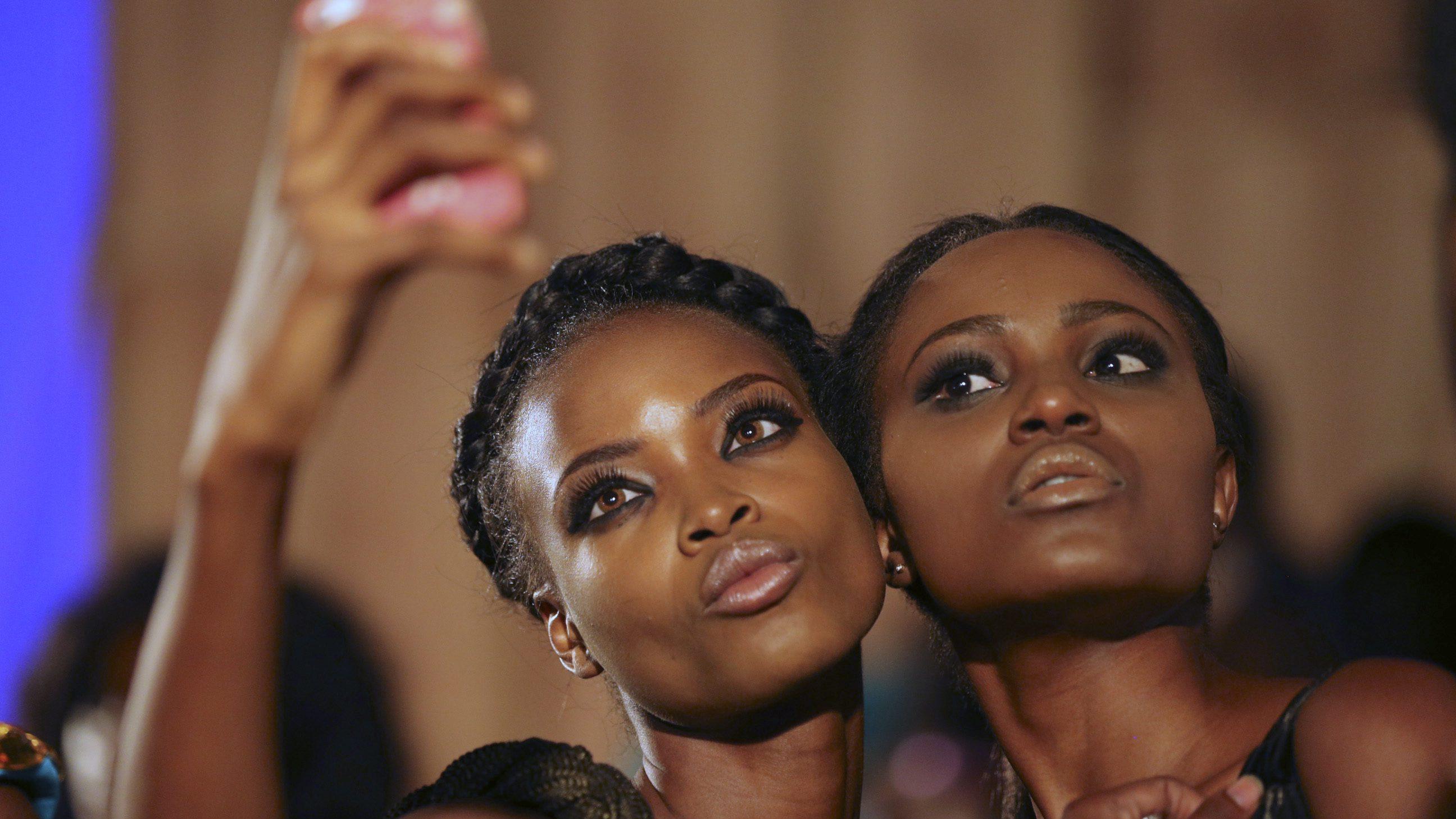 Models take a selfie backstage during Lagos fashion and design week October 29, 2014.