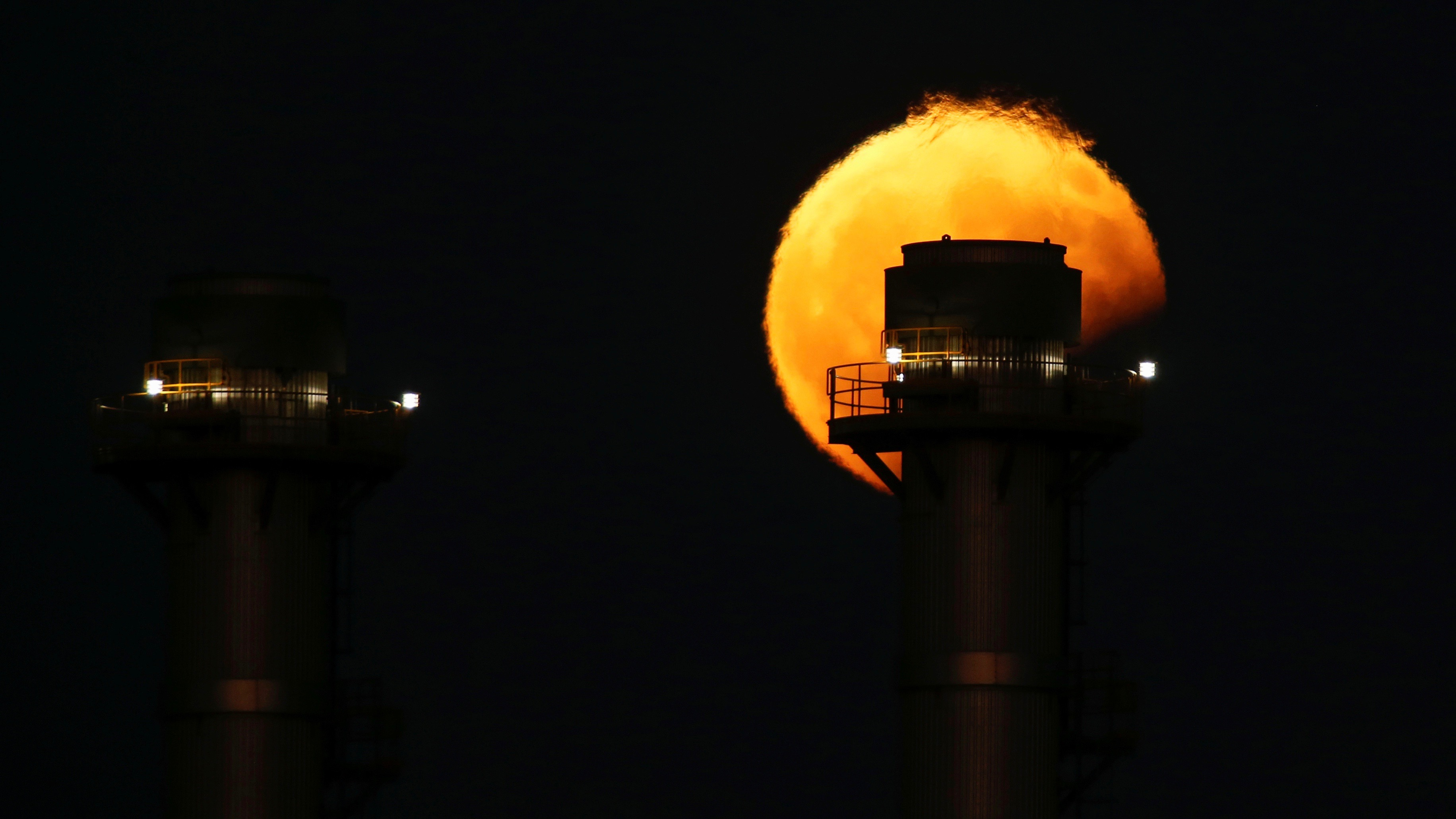 Moon rising by day behind a power plant.