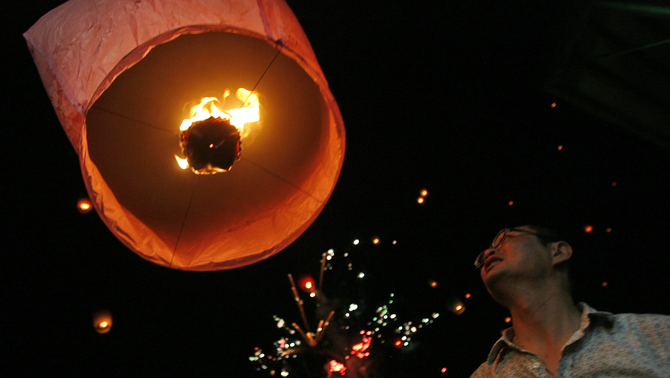 """A man releases a lantern during Chinese Valentine's Day or """"Qi Xi"""" festivities in Shifen August 25, 2007. Chinese Valentine's Day is usually celebrated on the seventh day of the seventh month of the lunar calendar but festivities were postponed this year due to Typhoon Sepat.  REUTERS/Nicky Loh (TAIWAN) - RTR1T2T3"""
