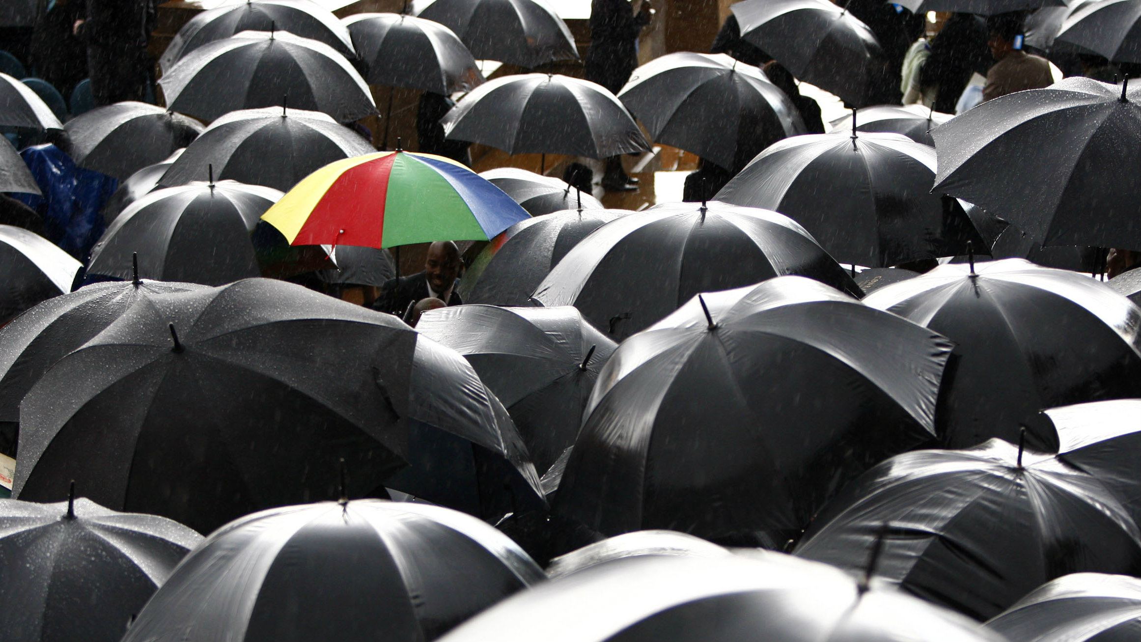 Guests attending President Jacob Zuma's inauguration at the Union Buildings in Pretoria shelter from the rain in South Africa, May 9, 2009. REUTERS/Steve Crisp