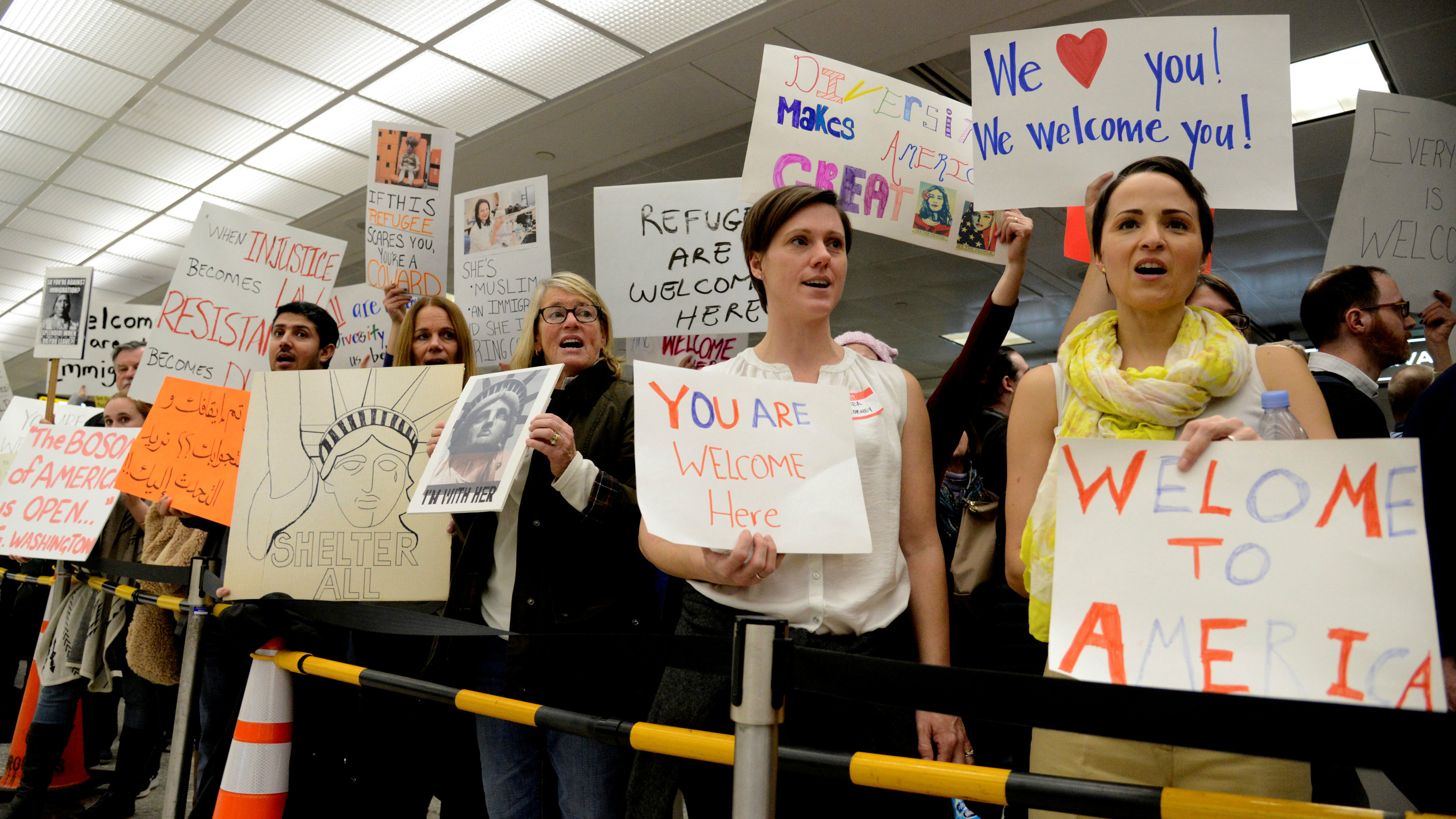 Dozens of pro-immigration demonstrators cheer and hold sign as international passengers arrive at Dulles International Airport, to protest President Donald Trump's executive order baring visitors, refugees and immigrants from certain countries to the United States, in Chantilly, Virginia, in suburban Washington, U.S., January 29, 2017.