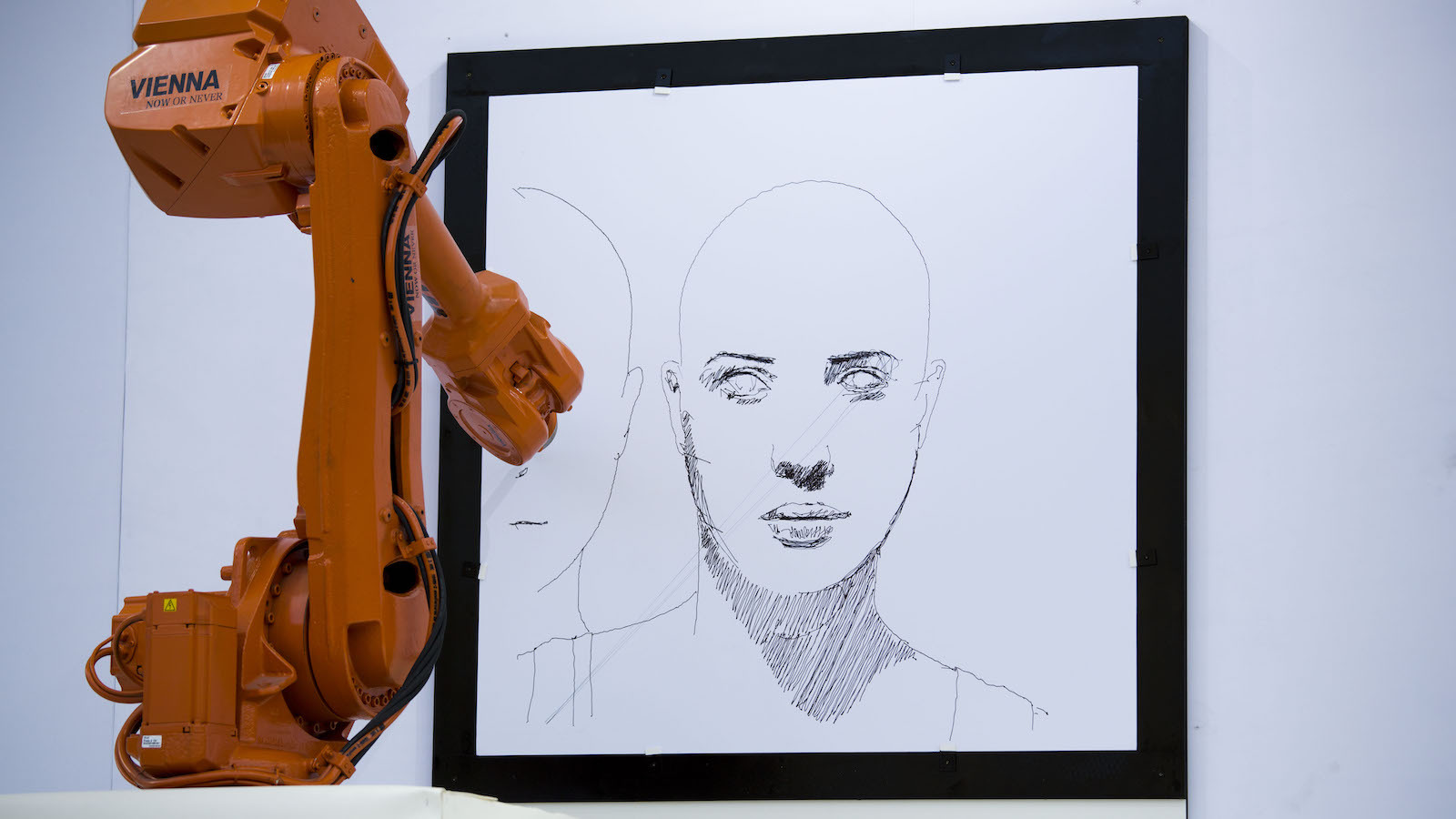 """A robot arm in Trafalgar Square, London, replicates  a drawing being created by Austrian artist Alex Kiessling  from Vienna, with another robot arm  simultaneously  replicating the work in Berlin, Thursday, Sept. 26, 2013.  The project has been given the title """"Long Distance Art"""" and utilizes the IRB 4600 robotic arms, produced by the company ABB for industrial manufacturing in areas such as automotive, plastics, metal fabrication and electronics.  (AP Photo/Matt Dunham)"""