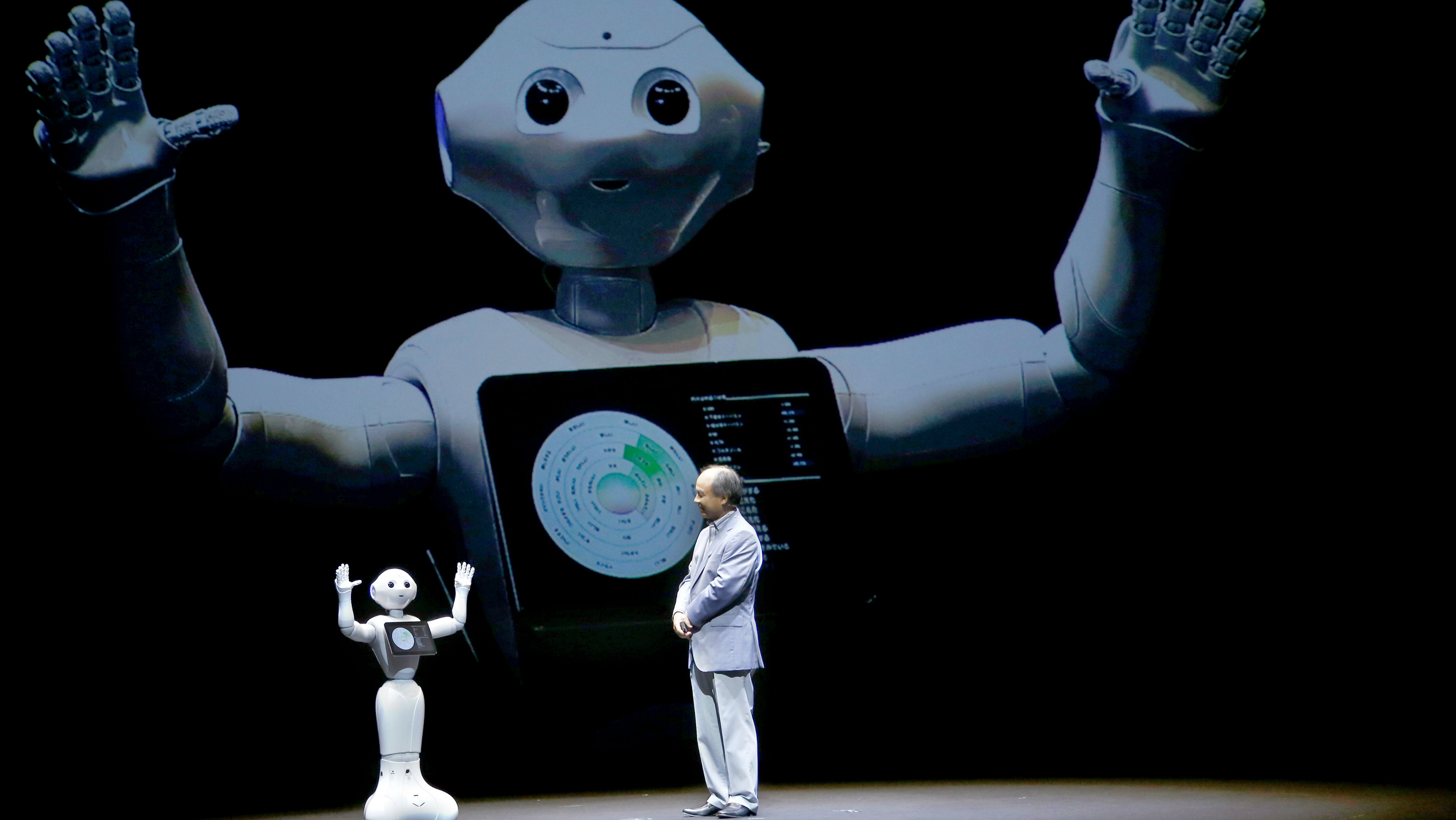 SoftBank Corp CEO Masayoshi Son speaks with the company's robot Pepper