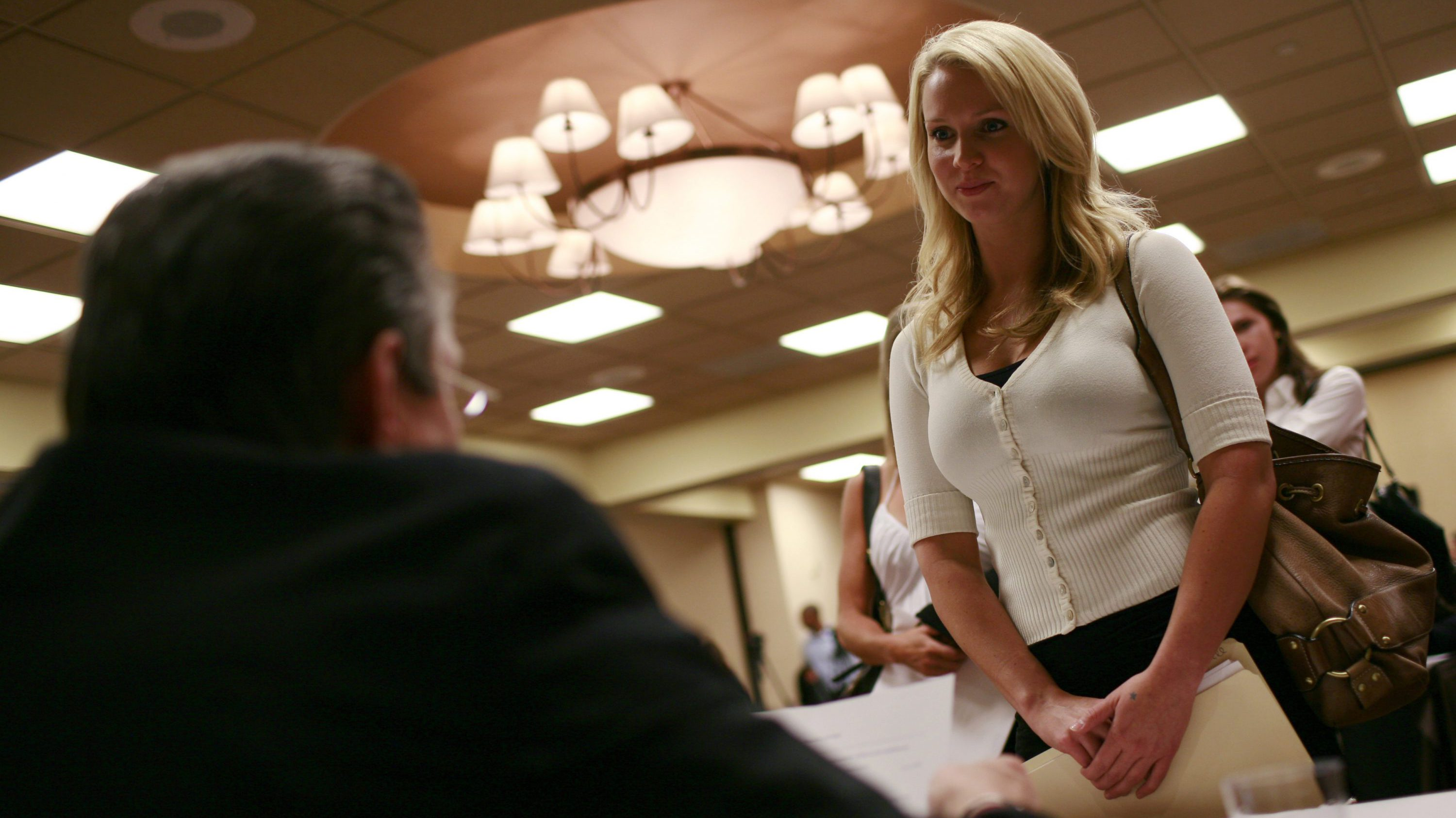A recruiting representative from a night club greets a potential employee during a job fair in San Francisco, California, July 20, 2009. Hundreds of people applied for 30 jobs as bartenders, exotic dancers and waitresses at several San Francisco strip clubs.