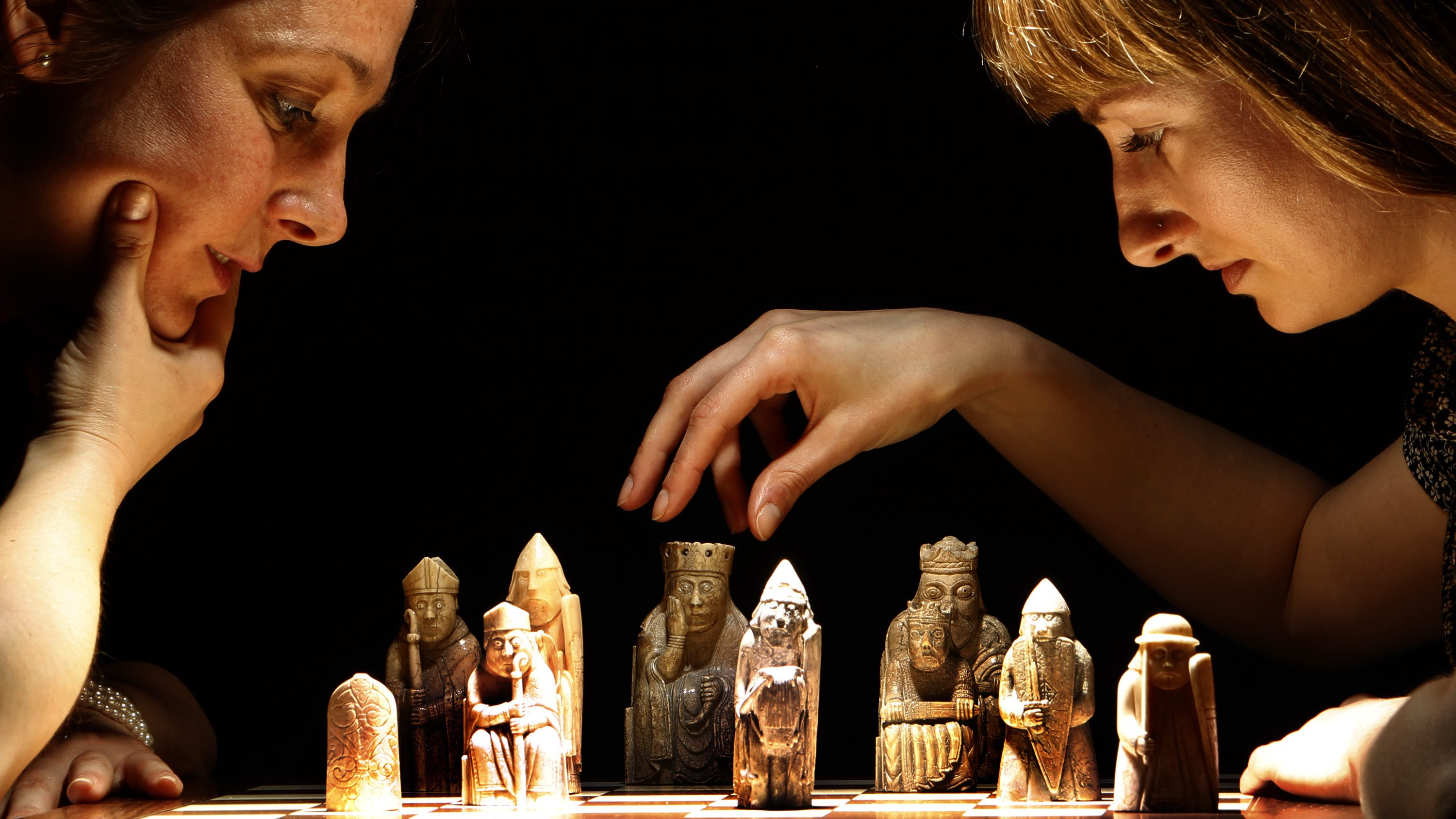 Jacqui Austin (L) and Lindsay McGill, from National Museums Scotland, pose for a game of chess for photographers with some of the Lewis Chessmen on display at the National Museum of Scotland in Edinburgh, Scotland May 20, 2010. The Lewis Chessmen consist of 93 pieces of elaborately worked walrus ivory and whales' teeth in the forms of seated kings and queens, mitred bishops, knights on their mounts, standing warders and pawns in the shape of obelisks. They are thought to have been made in Norway about AD 1150-1200 and were found on the Isle of Lewis, Outer Hebrides, Scotland in the late 1800's.