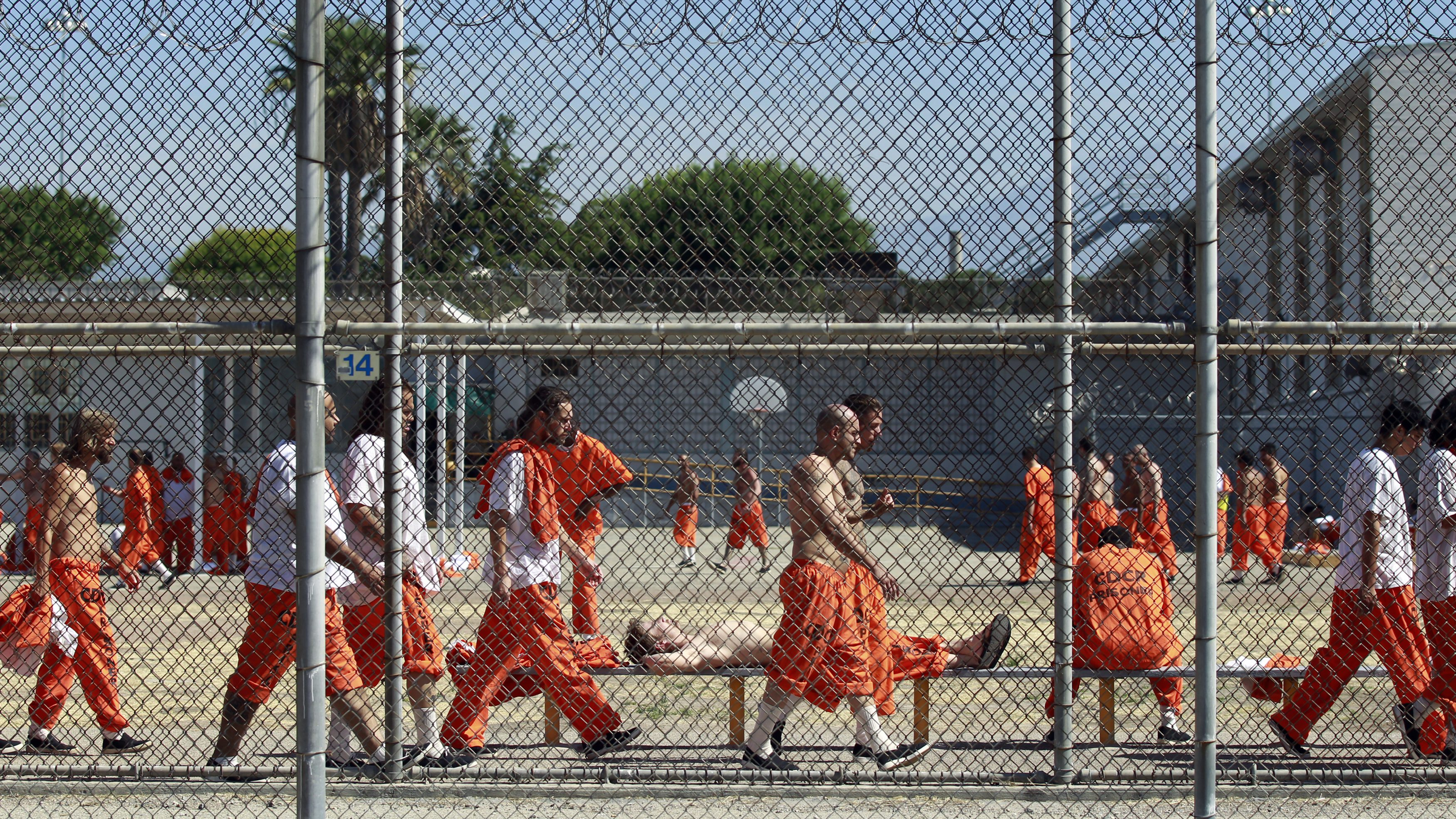 Inmates walk around an exercise yard at the California Institution for Men state prison