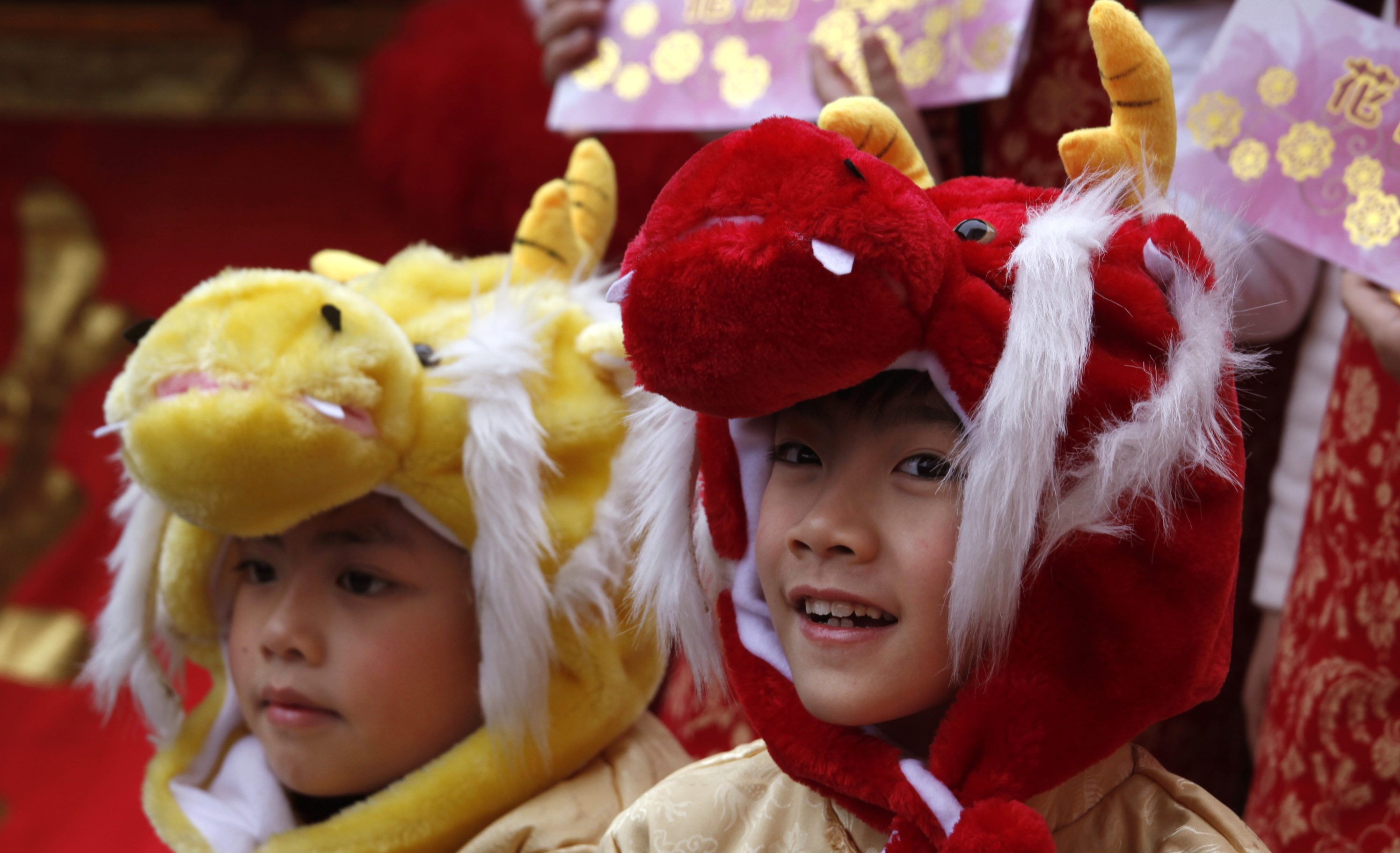 Boys wearing dragon hats take part in a Lunar New Year celebration outside a shopping mall in Hong Kong