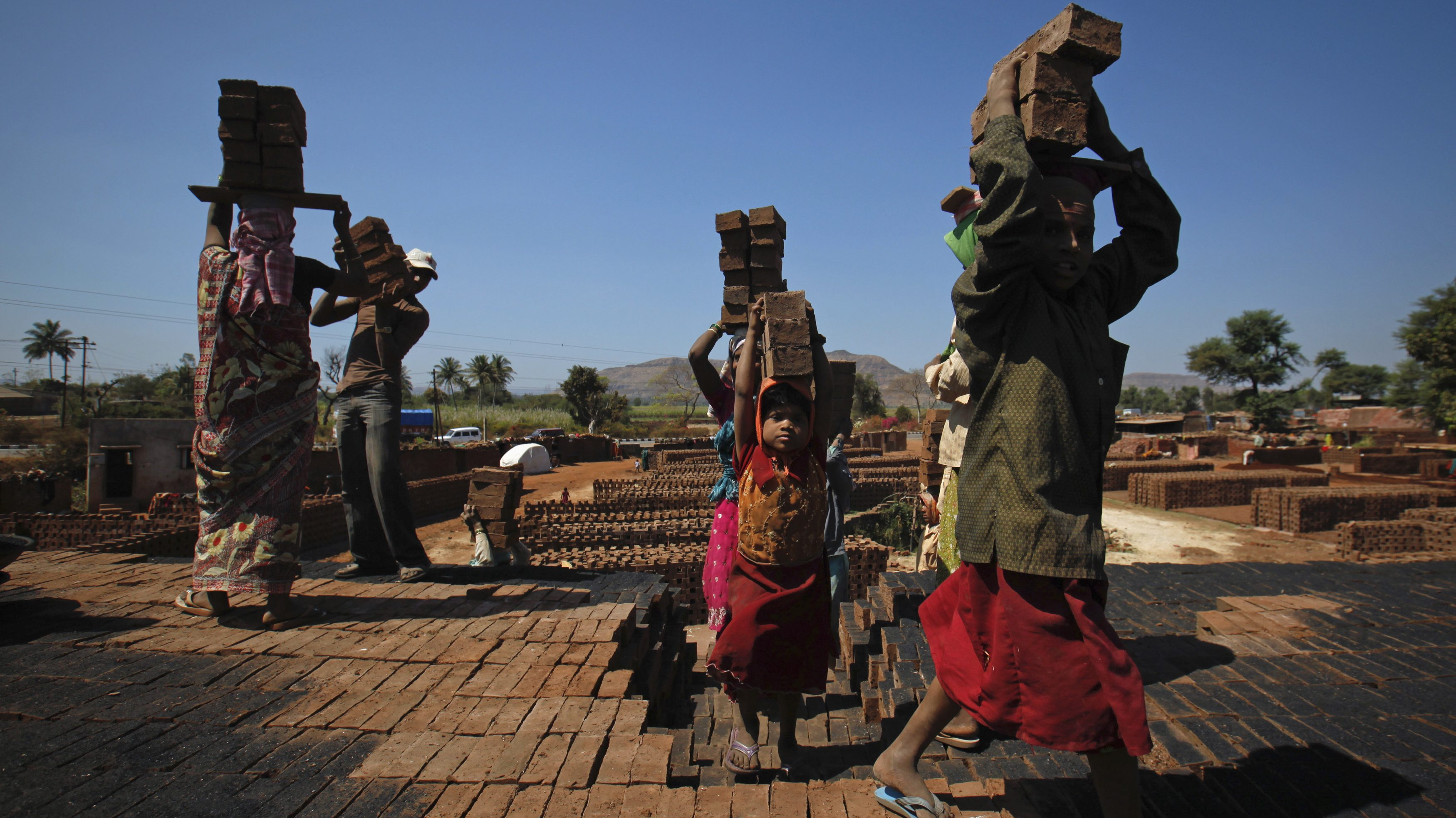 Girls carry bricks to be baked in a kiln at a brickyard on the outskirts of Karad in Satara district