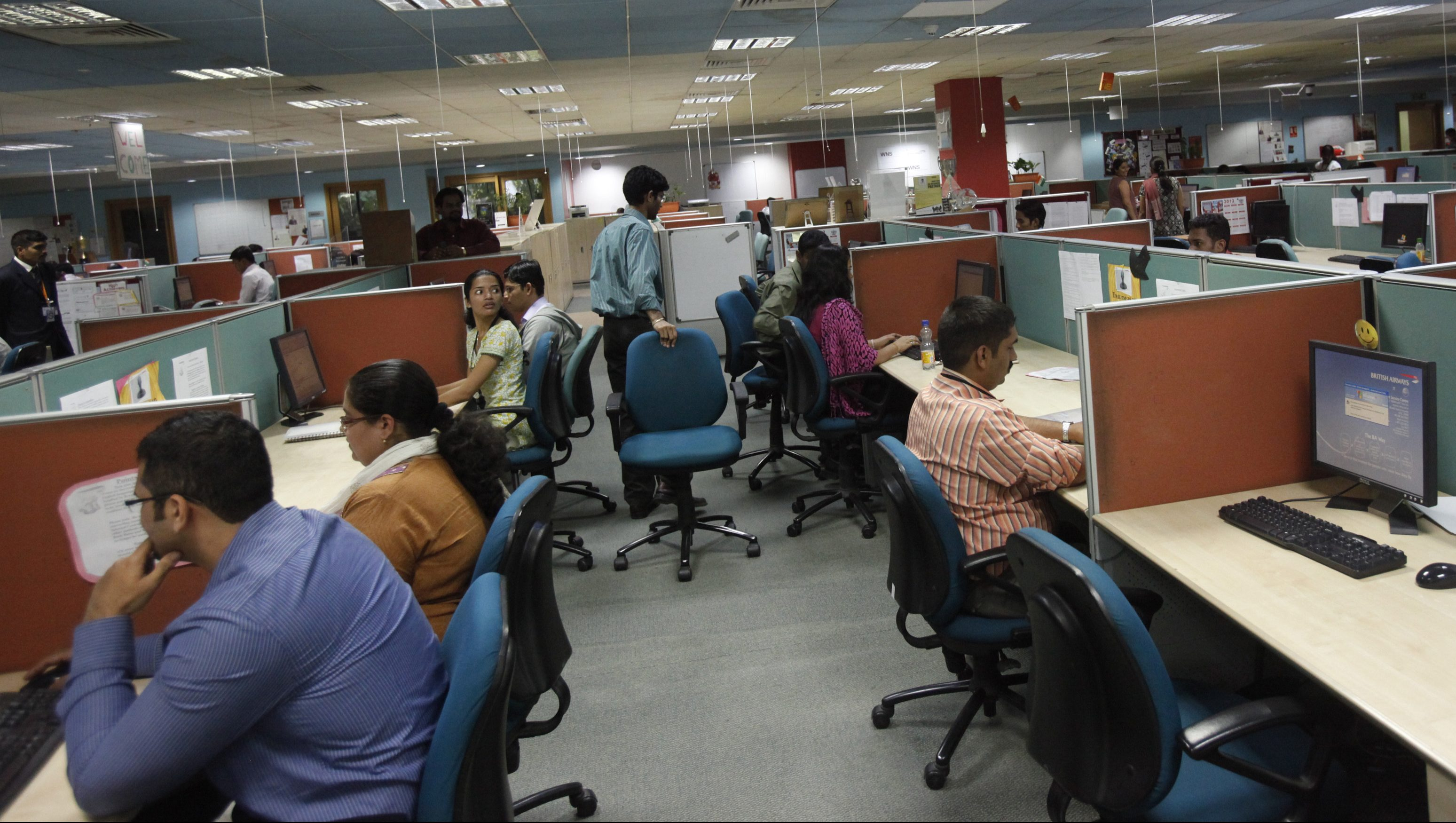Employees work on the floor of the outsourcing company WNS in Mumbai March 19, 2012. Indian back-office company WNS Holdings Ltd may launch the first of three customer-service centres in the United States over the next quarter, its CEO Keshav Murugesh said, as it looks to boost revenues in its second largest market. REUTERS/Vivek Prakash (INDIA - Tags: BUSINESS EMPLOYMENT) - RTR2ZKU9