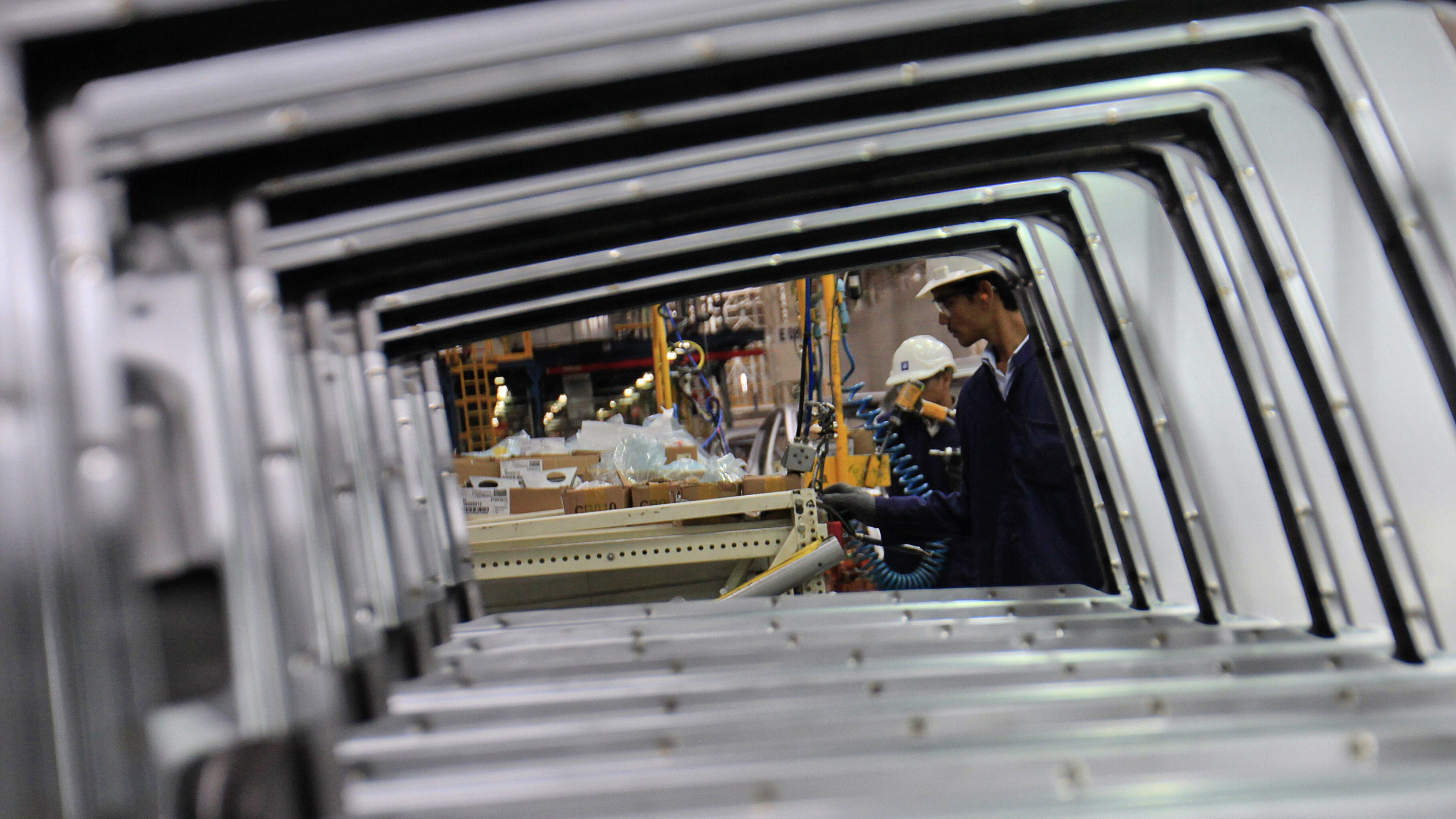 Employees are seen working through the doors of Chevrolet Beat cars on an assembly line at the General Motors plant in Talegaon