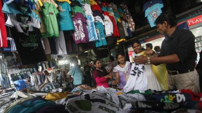 People shop for clothes at a roadside market in Kolkata
