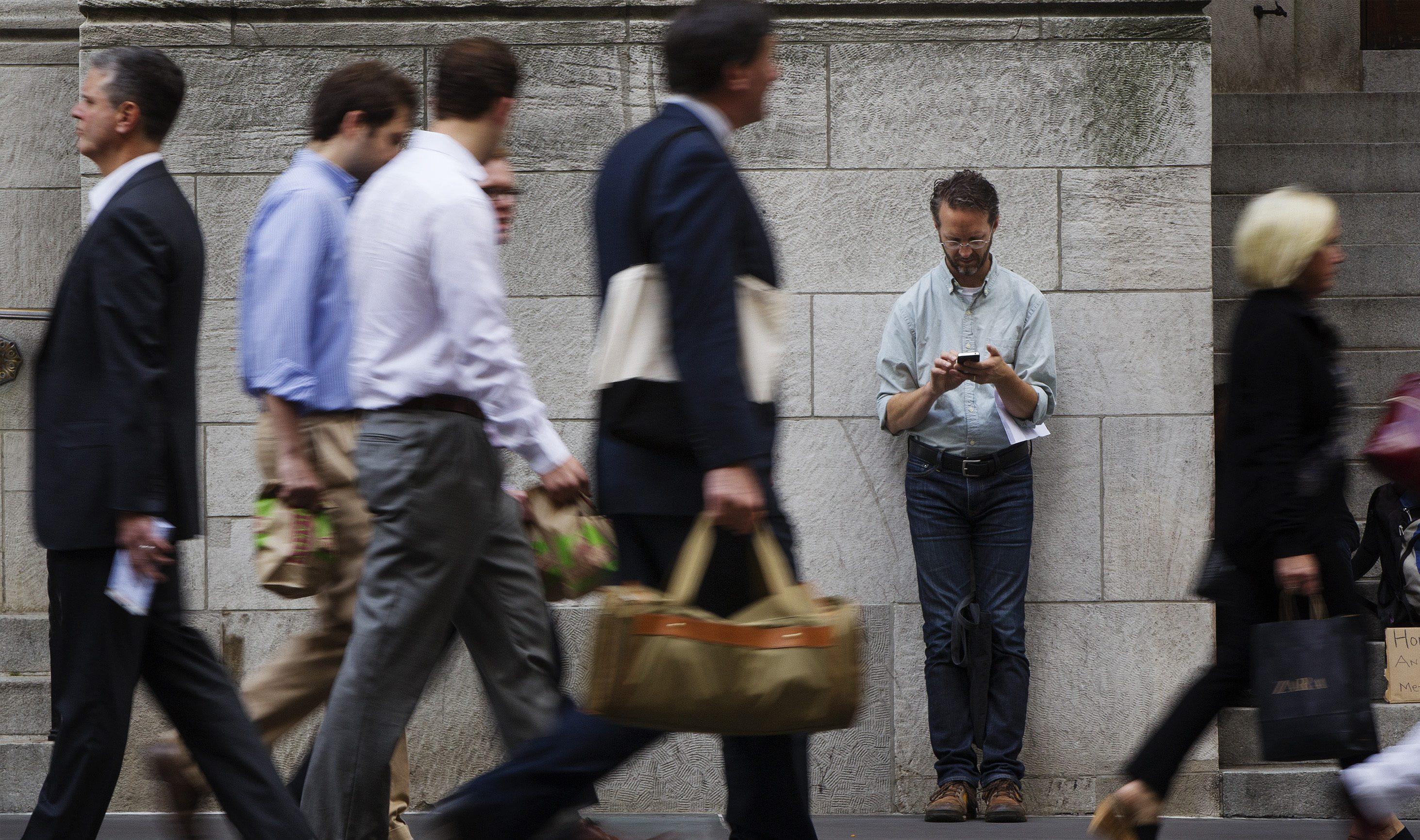 A man stops to lean against a building as pedestrians walk past while he looks down at his Apple iPhone on 5th Avenue in New York, September 20, 2012.