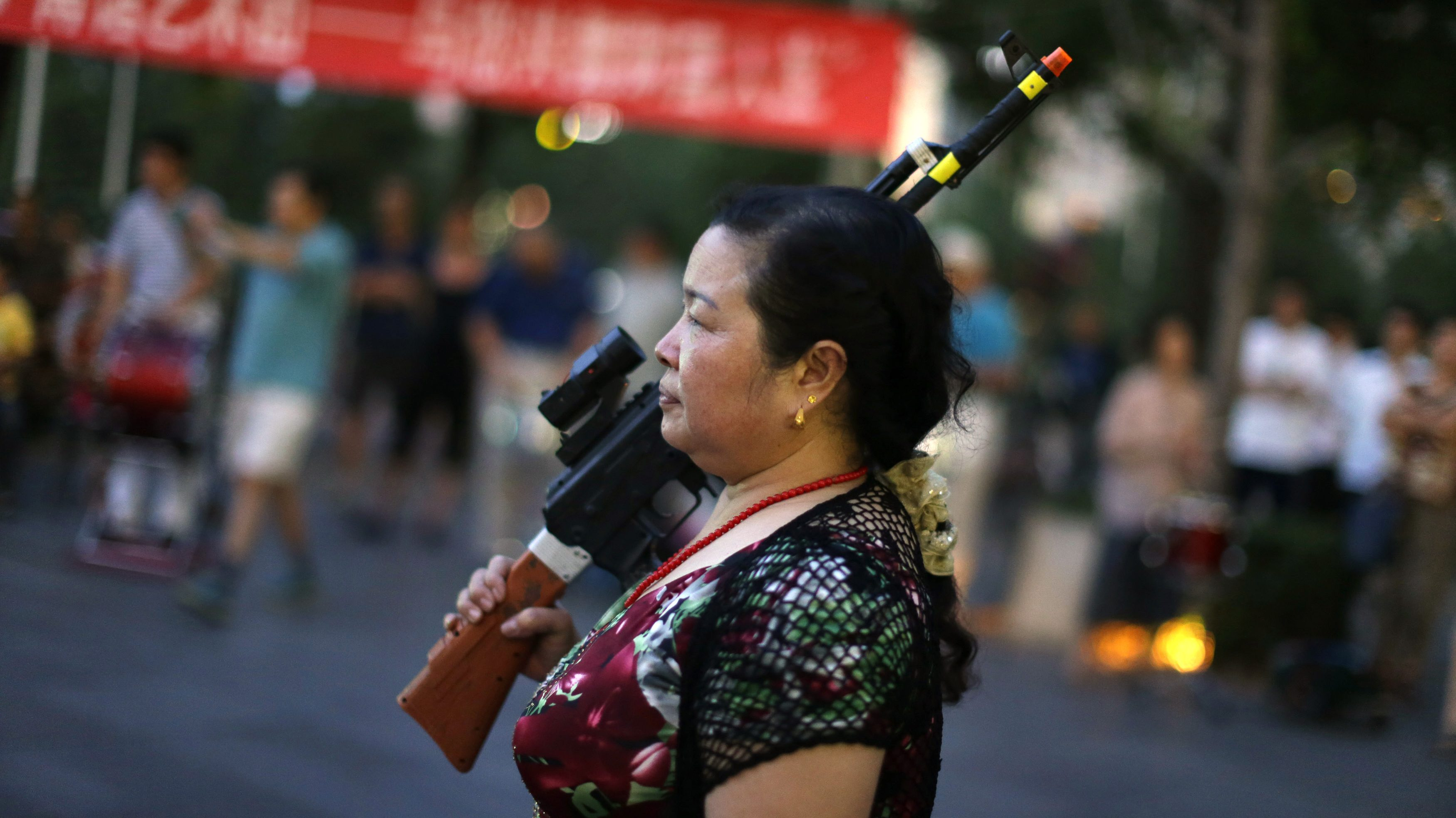 "A local woman holding a toy gun prepares to dance to revolutionary songs as part of her daily exercise at a square outside a shopping mall in Beijing, June 27, 2014. About 30 local residents formed this ""Nanguan"" art group that enjoys performing and dancing to revolutionary songs as part of their nightly fitness activity. Picture taken June 27, 2014."
