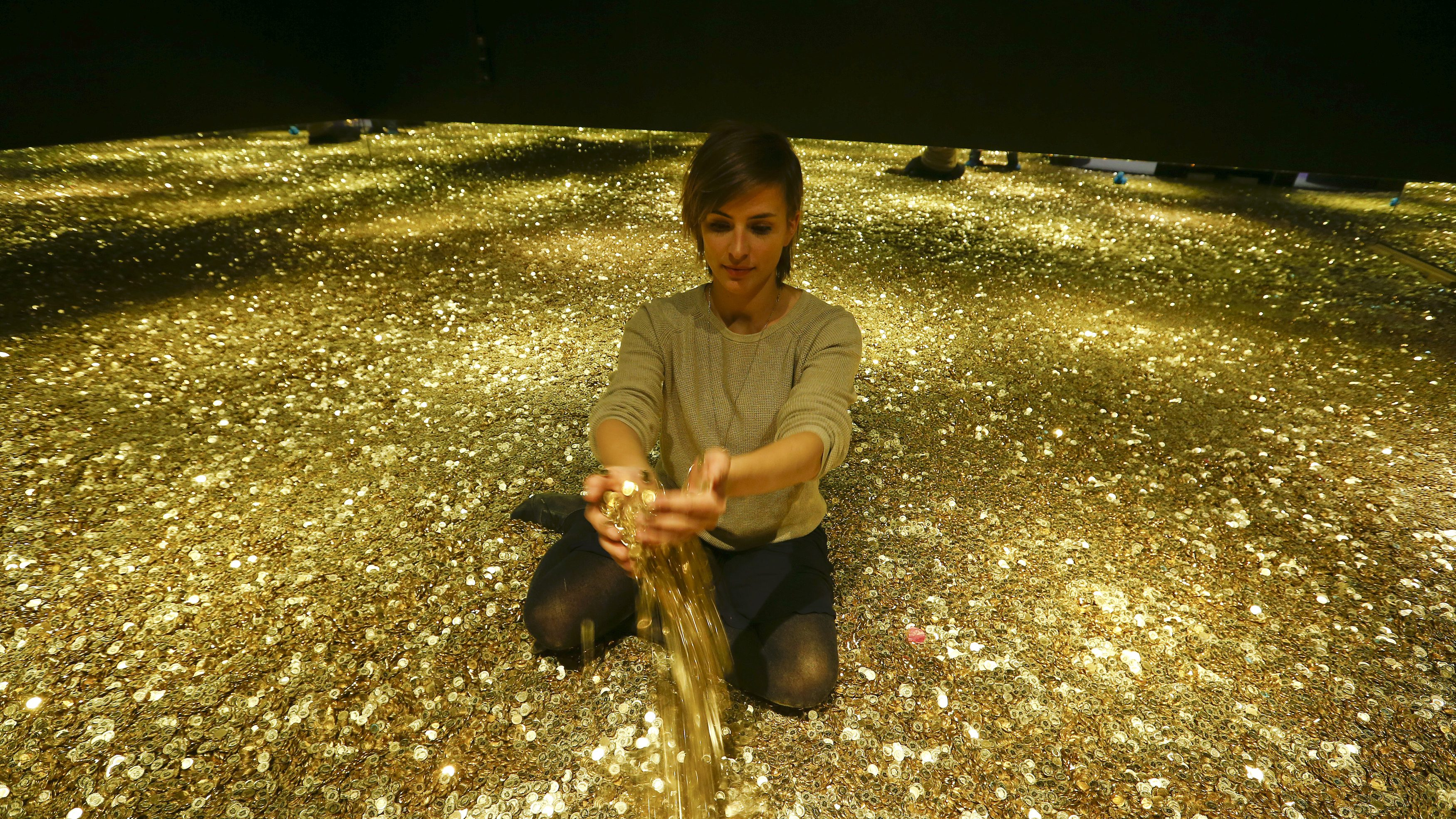 "Sonja Enz of the Stapferhaus, an event place for contemporary exhibitions, holds coins in her hands as she sits in a room filled with 4 million Swiss five cent coins during a media preview of the exhibition ""Geld - Jenseits von Gut und Boese"" (Money -beyond good and evil) in the town of Lenzburg west of Zurich November 14, 2014. The exhibition at the Stapferhaus is opened to the public from November 15 to November 29, 2015.  REUTERS/Arnd Wiegmann (SWITZERLAND  - Tags: SOCIETY ENTERTAINMENT TPX IMAGES OF THE DAY)   - RTR4E4WT"