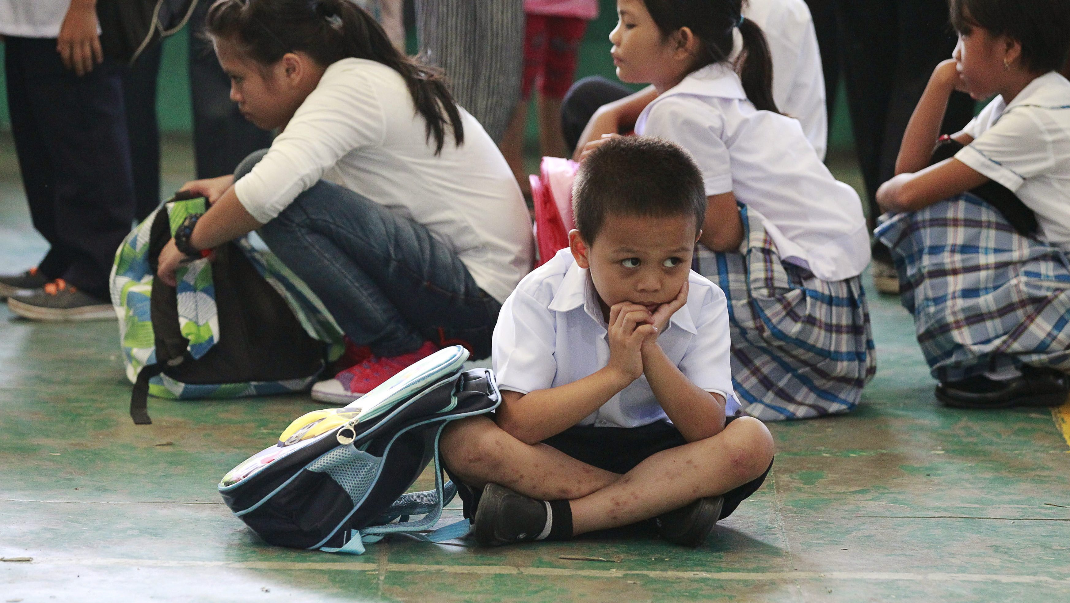 A boy sits on the floor as he waits with other students for the morning flag ceremony at Baclaran Elementary School in Paranaque City, metro Manila June 1, 2015. An estimated 24 million public school students in the primary and secondary levels attend the opening of classes nationwide, local media