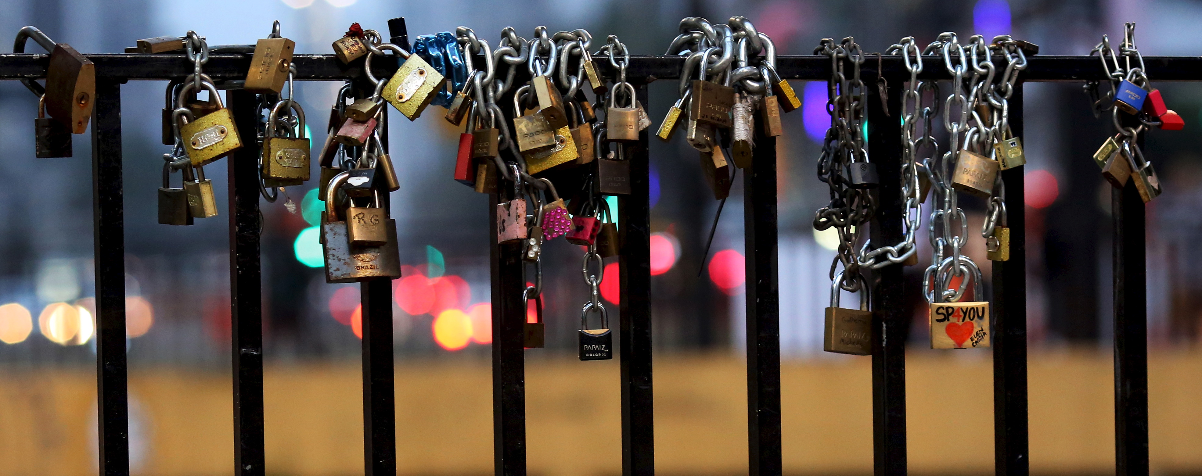 """""""Love locks"""" are seen attached to an iron grill in a viaduct at Paulista Avenue in Sao Paulo's financial centre, June 2, 2015.  REUTERS/Paulo Whitaker - RTR4YKFY"""