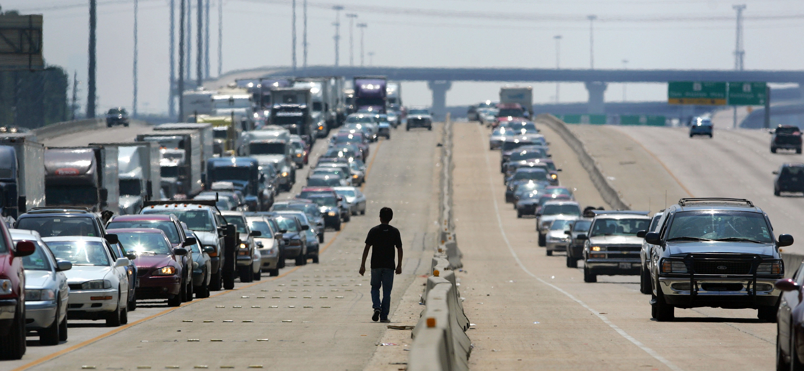 A man walks on a highway as thousands of cars try to evacuate in advance of Hurricane Rita in north Houston September 22, 2005. Hurricane Rita weakened to a still dangerous Category 4 storm with maximum sustained winds of 150 miles per hour, the U.S. National Hurricane Center said in an advisory on Thursday. REUTERS/Carlos Barria - RTRP2ZJ