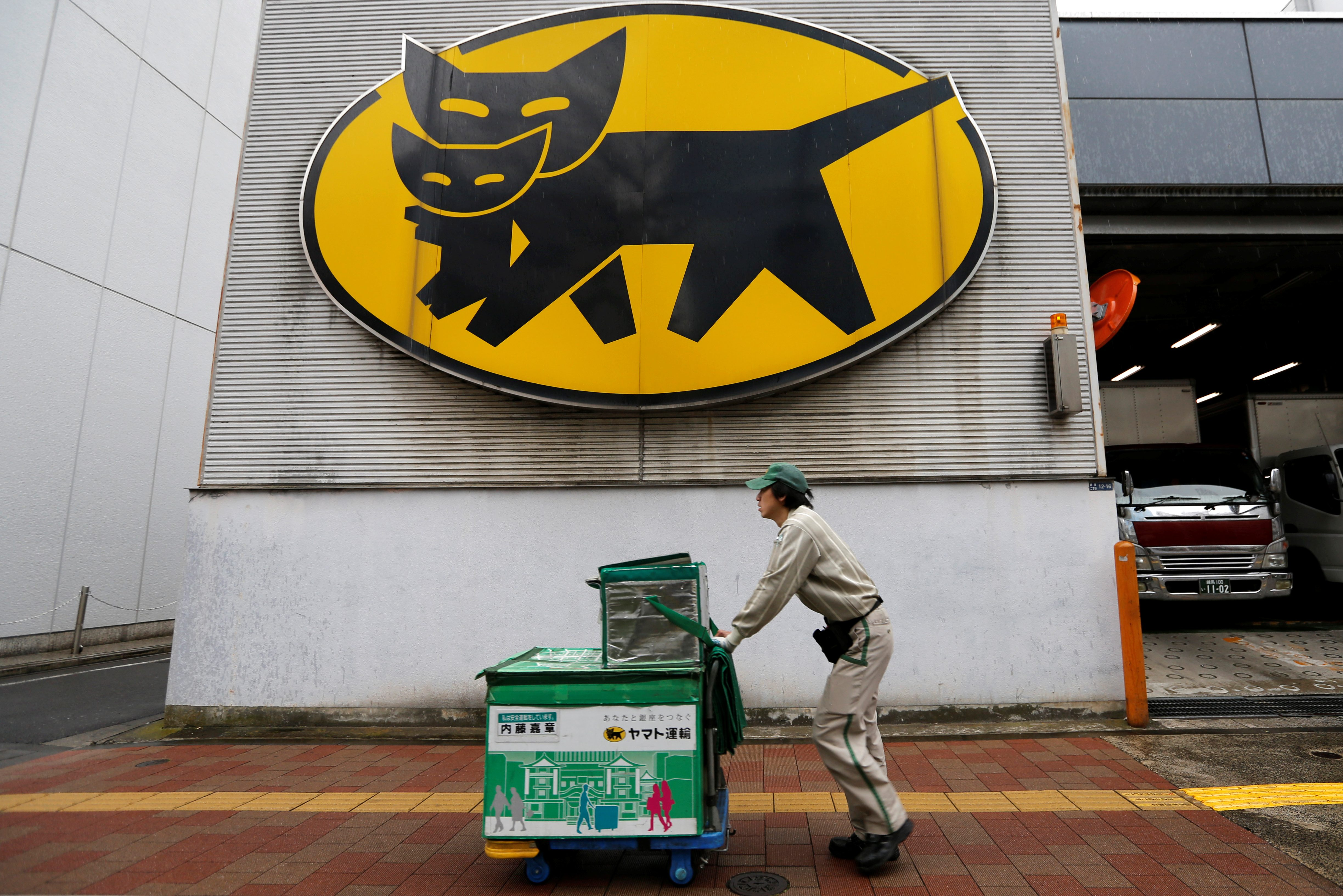 Deliverer of Yamato Transport Co is seen under the company's logo at a business district in Tokyo