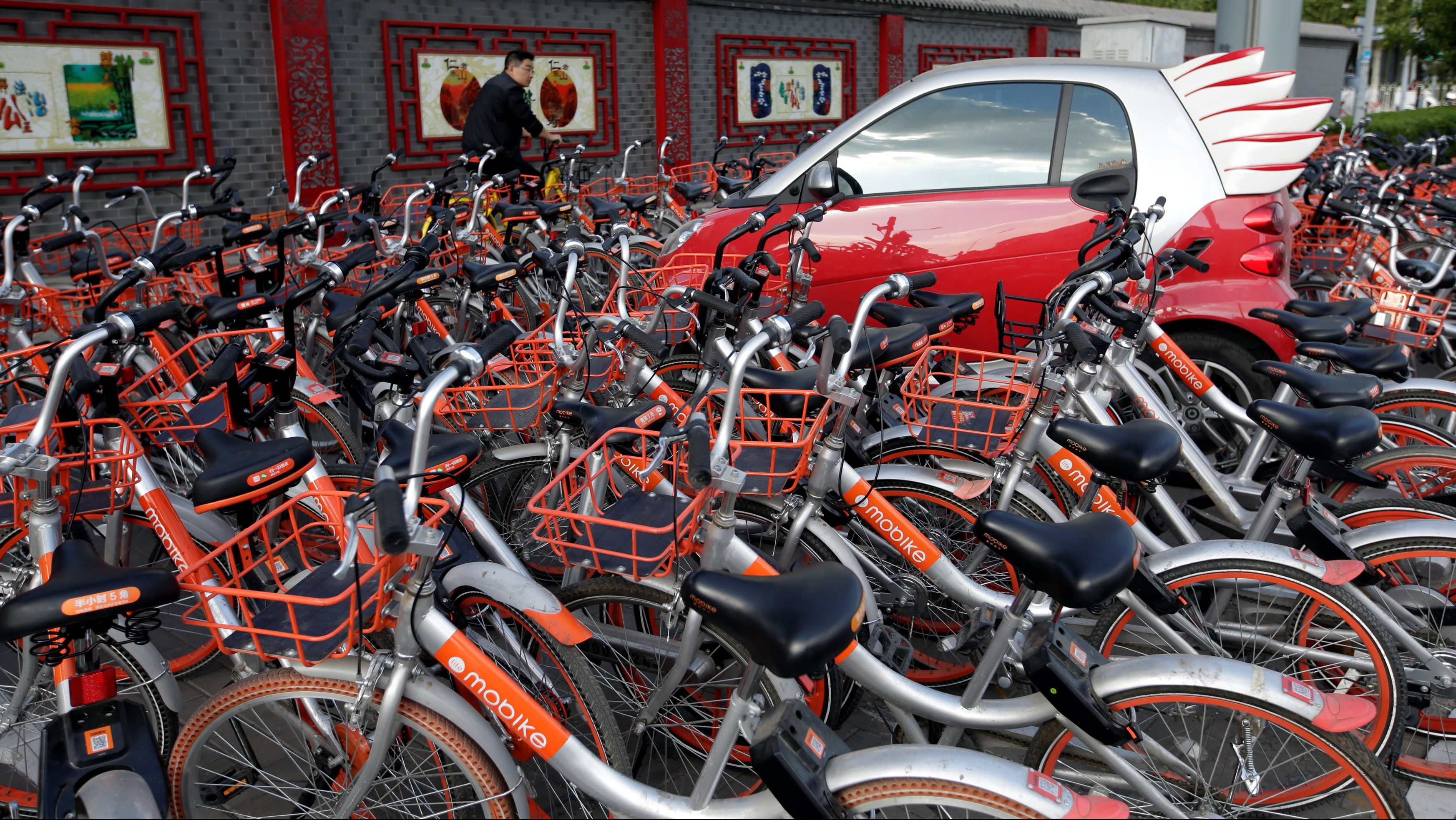 Mobike's shared bikes are parked around a car in Beijing, China April 21, 2017.