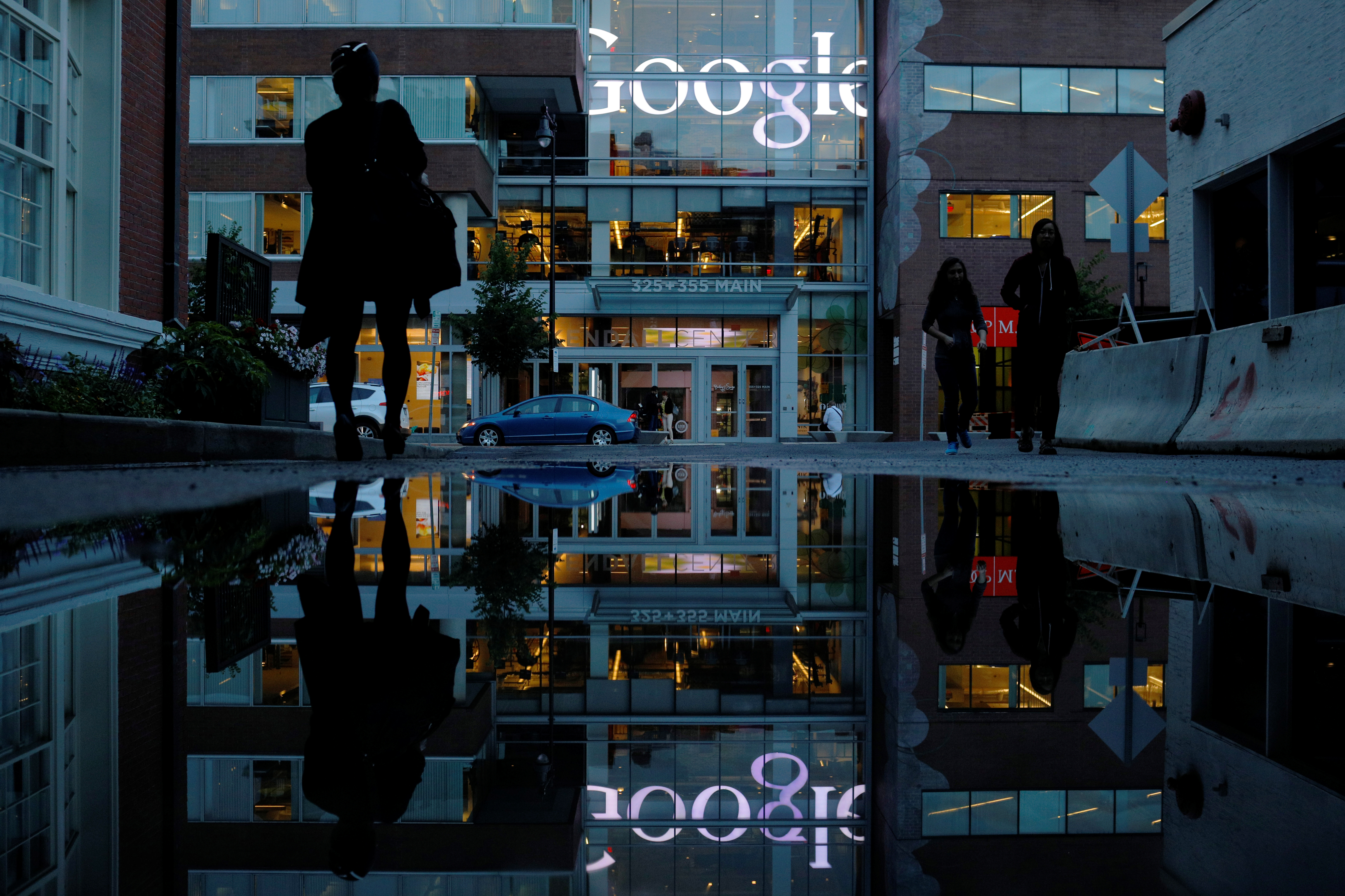 The Google sign is reflected in a rain puddle outside their offices.