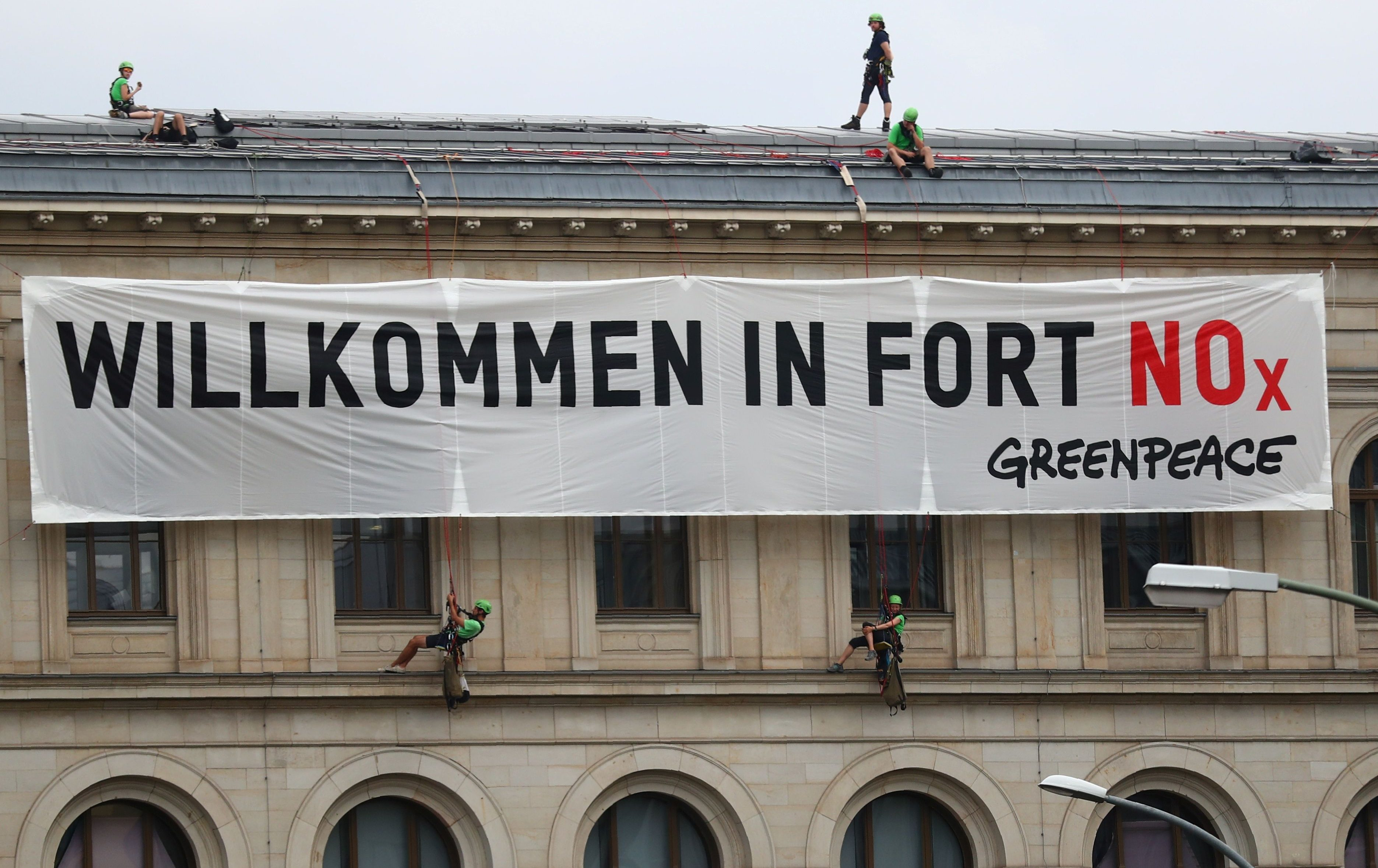 """Activists of Greenpeace attach a banner that reads """"Welcome to Fort NOx"""" to Germany's Federal Ministry of Transport and Digital Infrastructure before ministers and car executives will meet on Wednesday to agree ways to cut inner-city pollution to try to stave off bans on diesel cars and restore the tarnished reputation of the country's auto industry in Berlin, Germany, August 2, 2017"""