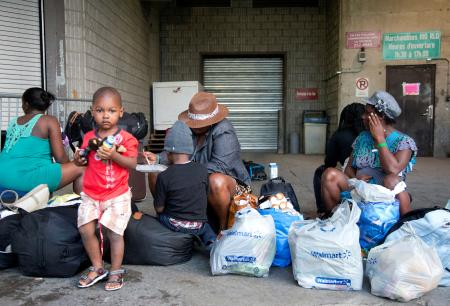 A group of Haitian asylum seekers sit with shopping bags outside the Olympic Stadium, which is being used for temporary housing for asylum seekers, in Montreal