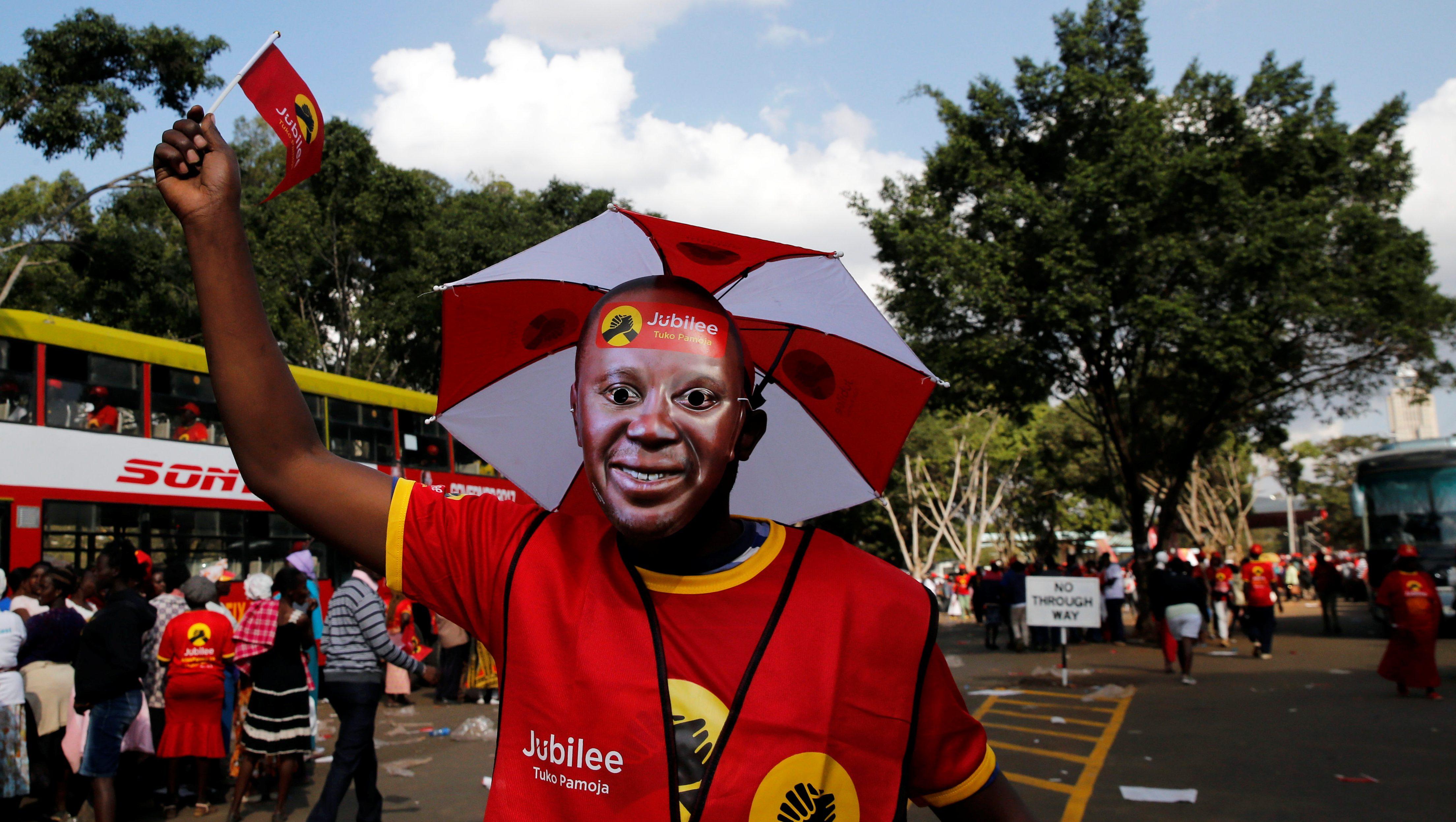 A supporter of Kenya's President Uhuru Kenyatta wears his mask during a Jubilee Party campaign rally at Uhuru park in Nairobi, Kenya August 4, 2017.