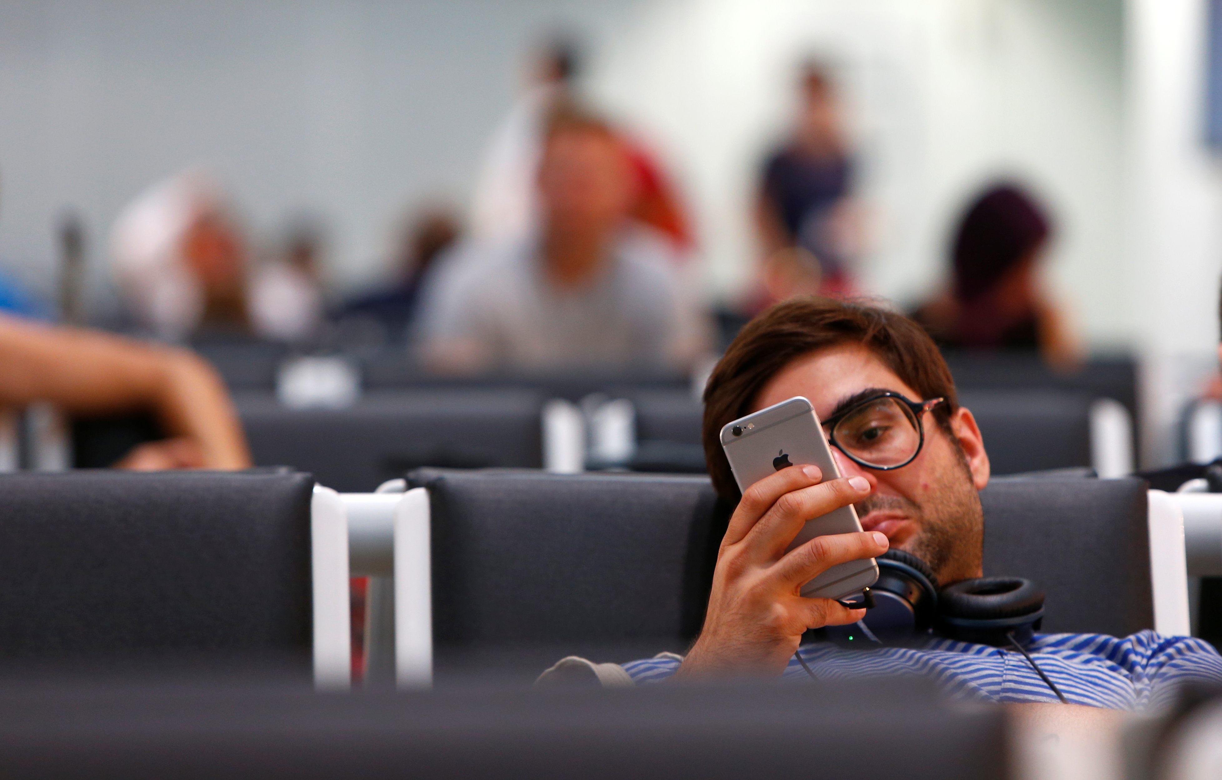 Man uses iphone while waiting for his airplane at Munich airport.