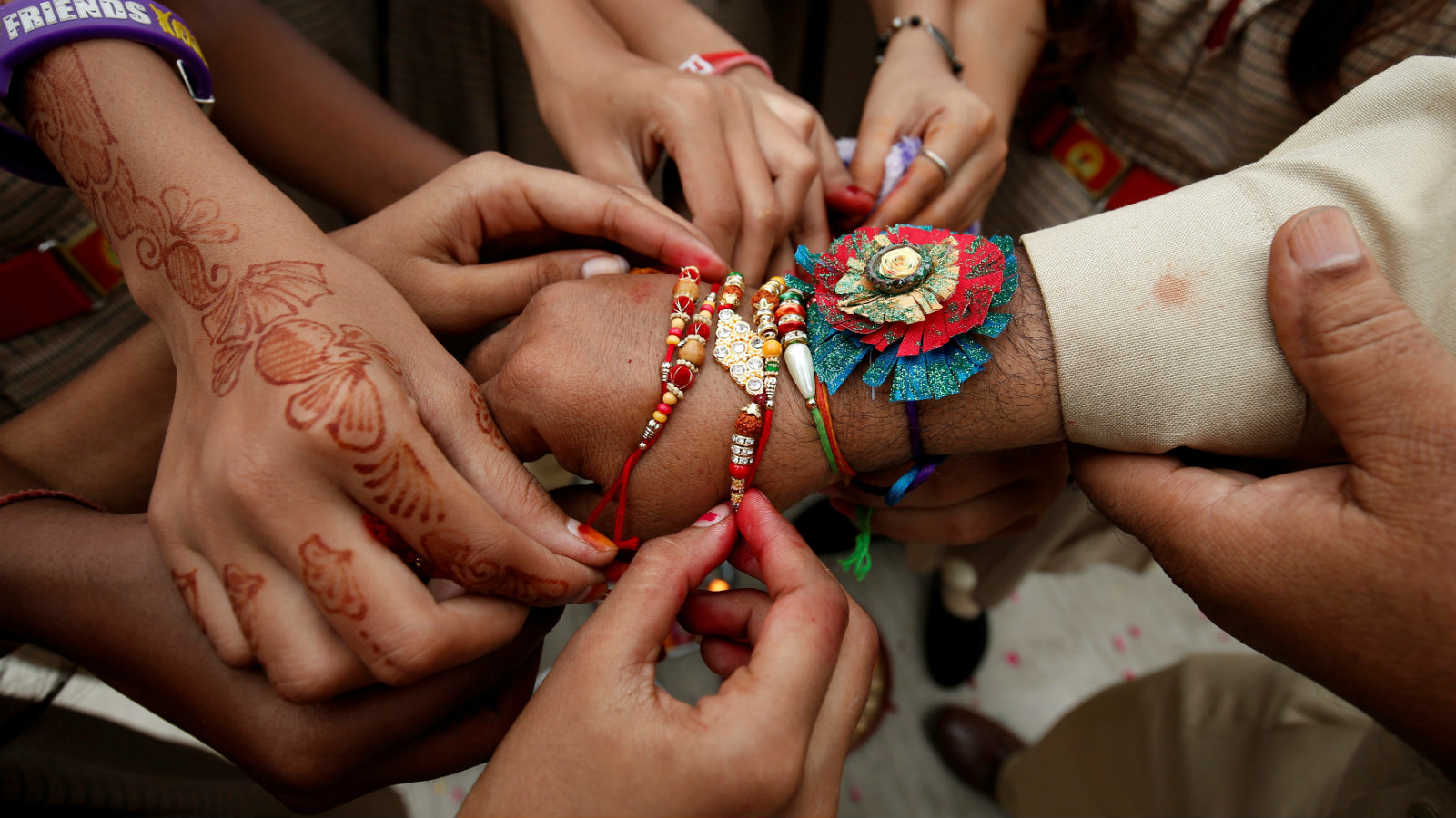 Schoolgirls tie rakhis, sacred threads, onto the wrist of a police officer on the occasion of Rakshabandhan, in Ahmedabad.