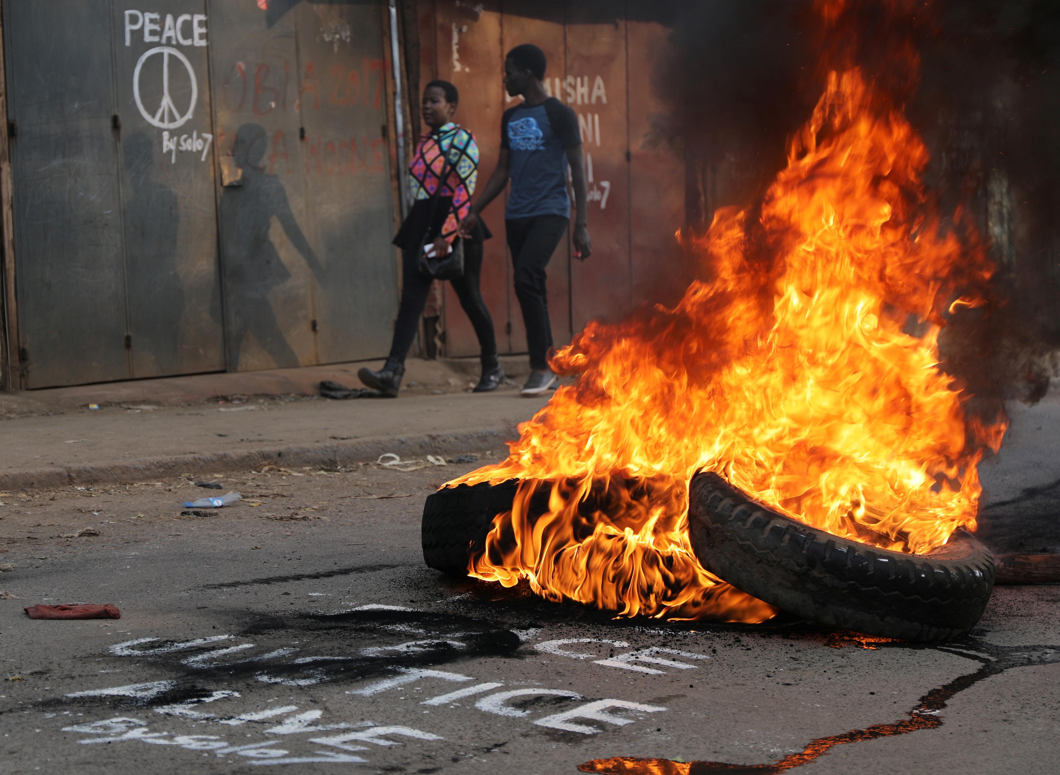 People walk near flaming tyre barricade in Kibera slum in Nairobi, Kenya, August 9, 2017.