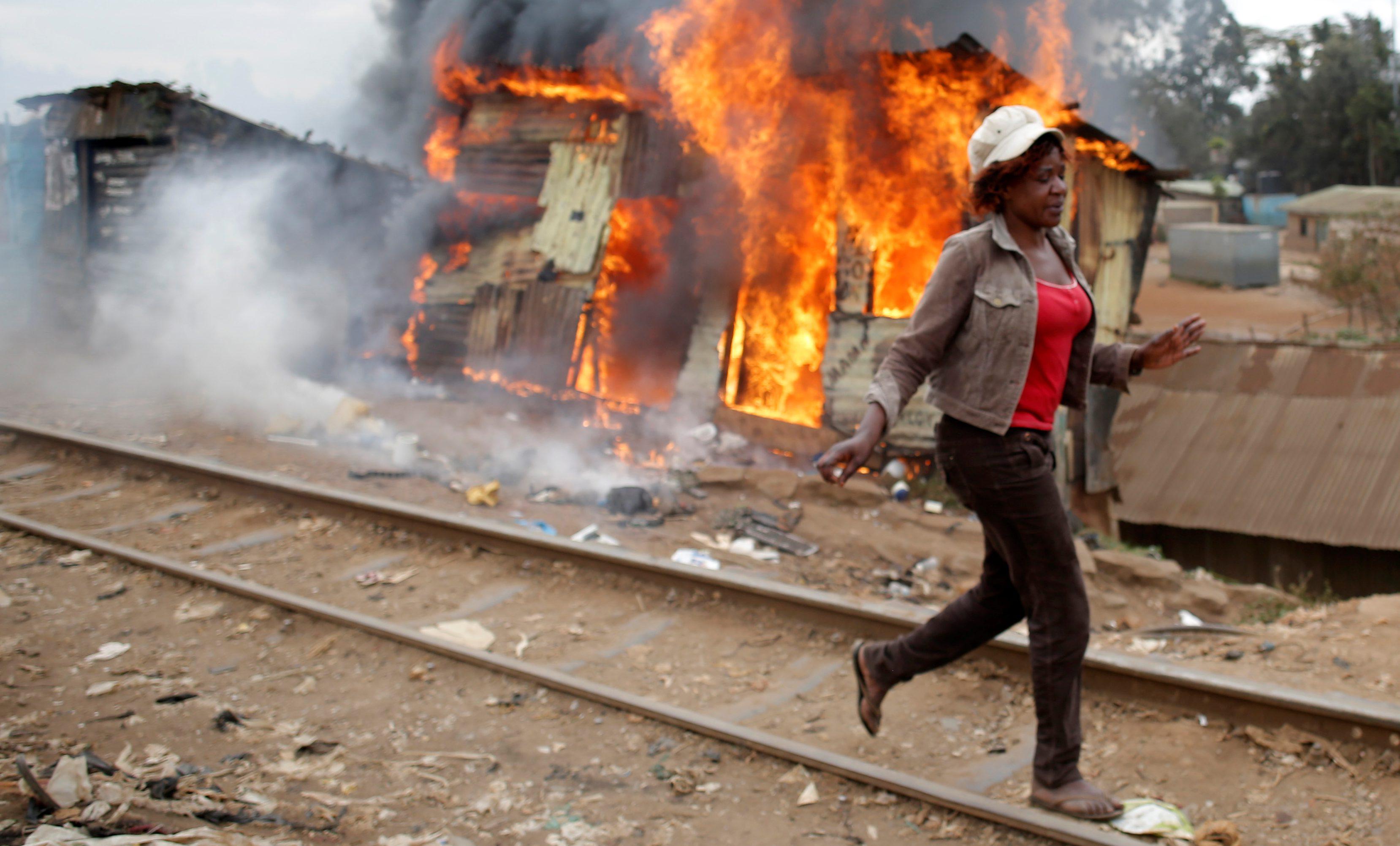 A woman walks past a burned shack, in Kibera slum, in Nairobi, Kenya.