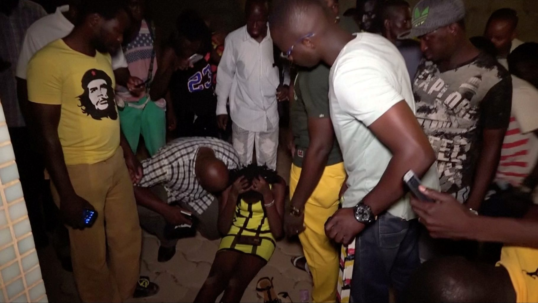 A wounded restaurant customer sits on the ground following an attack by gunmen on a restaurant in Ouagadougou, Burkina Faso, in this still frame taken from video August 13, 2017.