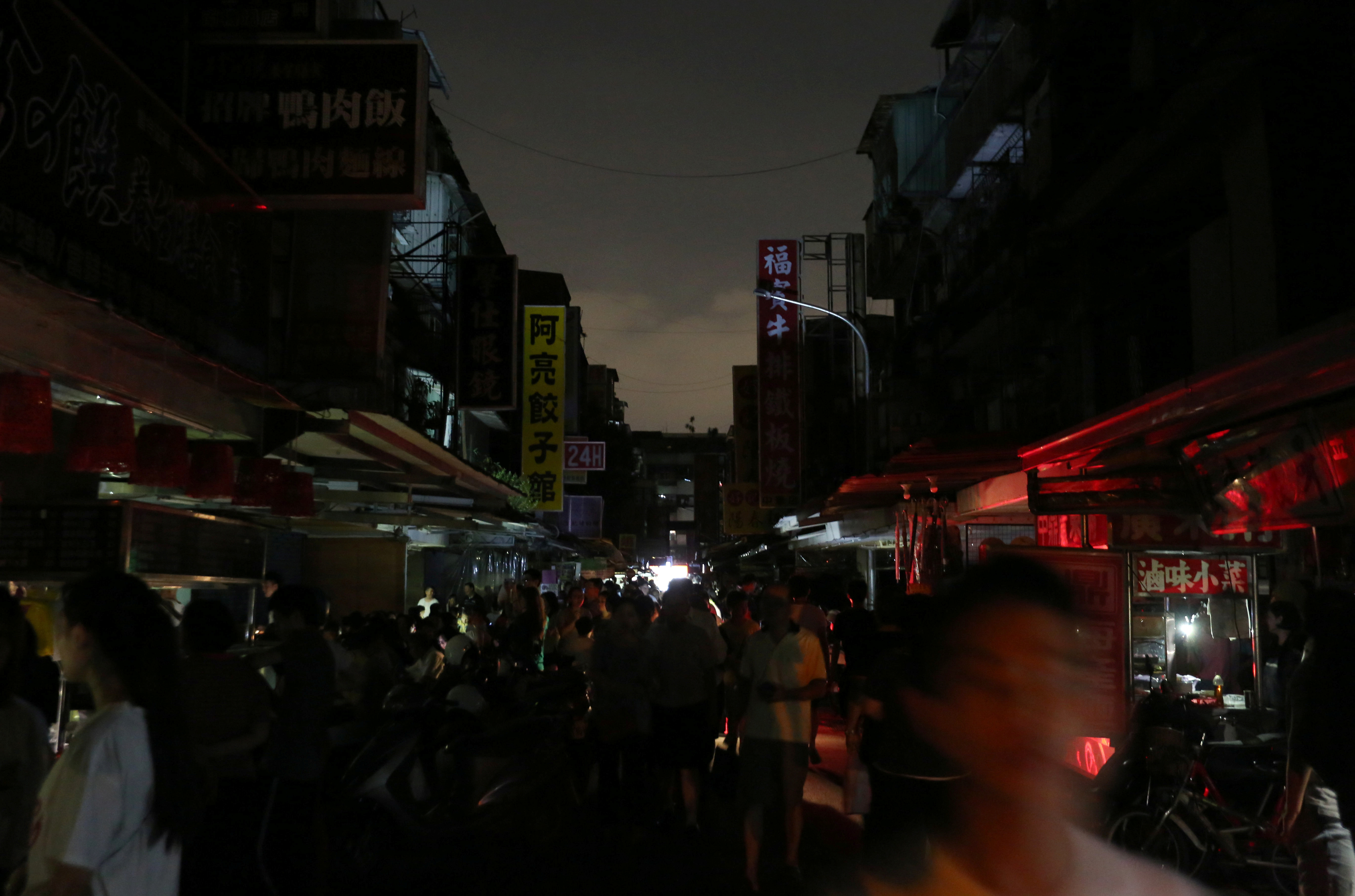 People walk on a street during a massive power outage in Taipei, Taiwan August 15, 2017.